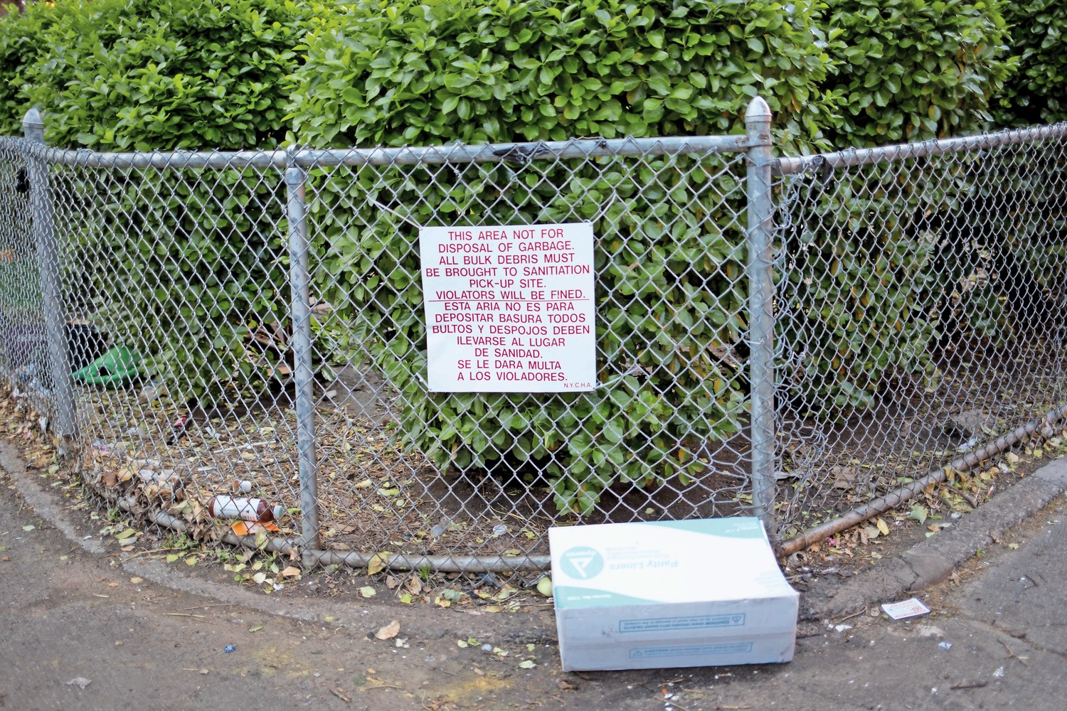 Garbage rests next to a sign notifying tenants that garbage is not supposed to be dumped in that area. On May 26, Tony Edwards, the president of the Marble Hill tenants association, will lead a neighborhood clean-up.