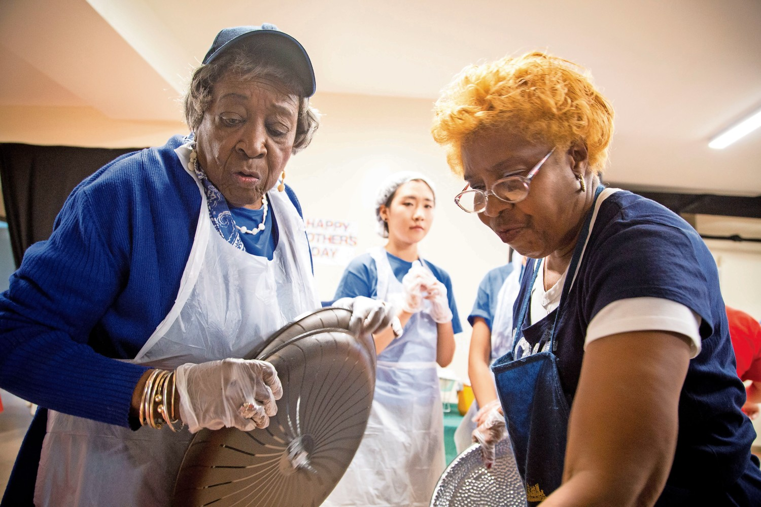 Gloria Hobbs, left, and Norma Cornish pick up trays, and get ready to serve food at the Caldwell Temple Soup Kitchen.