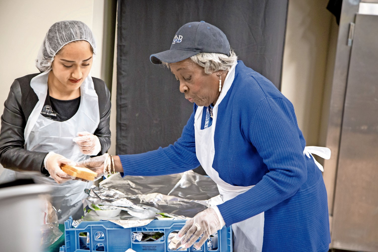 Gloria Hobbs grabs bread from another volunteer, and brings it to an attendee of the Caldwell Temple Soup Kitchen.
