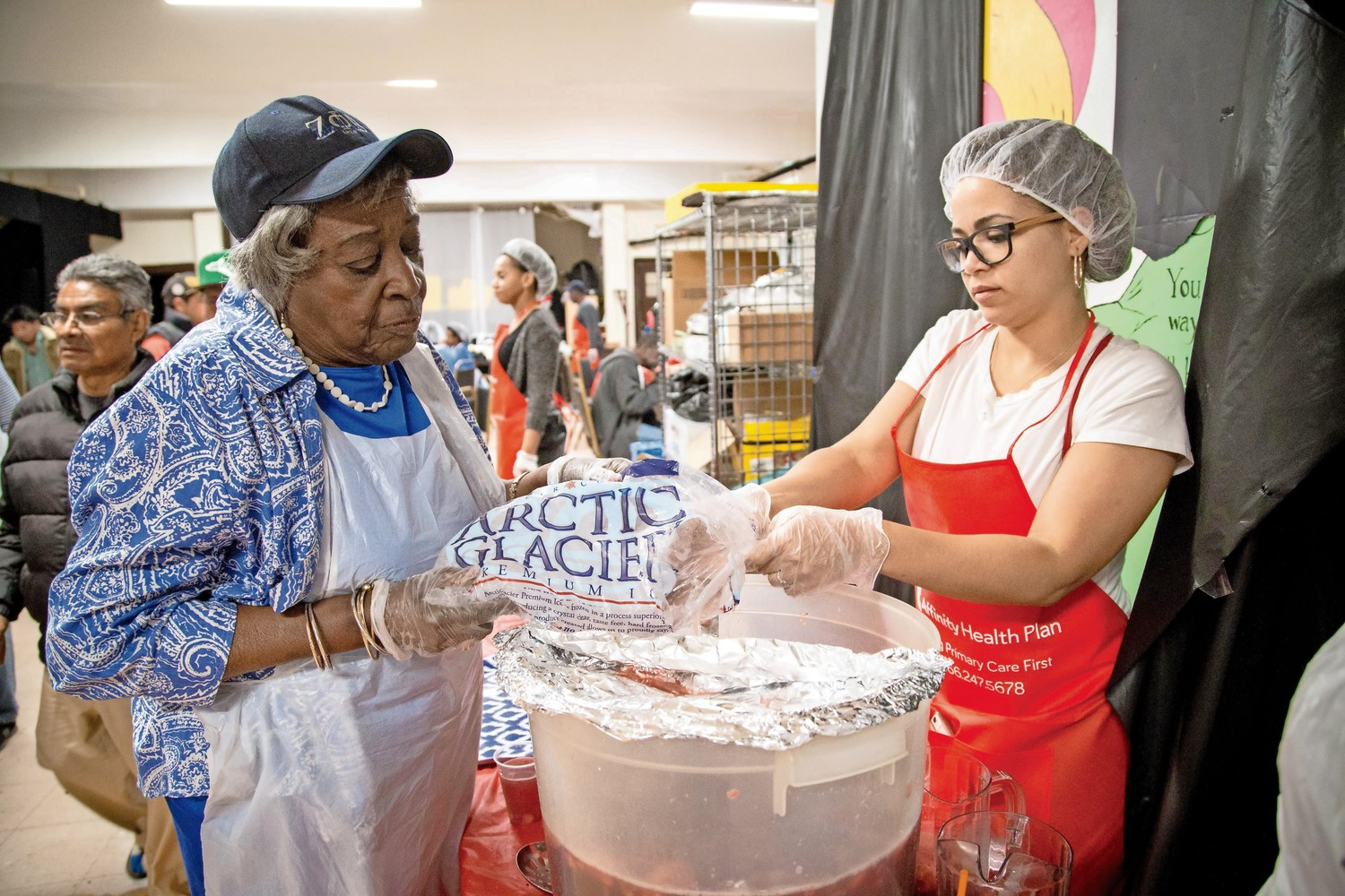Gloria Hobbs, left, shows Luz Sanchez how to mix and serve the punch at the Caldwell Temple Soup Kitchen.