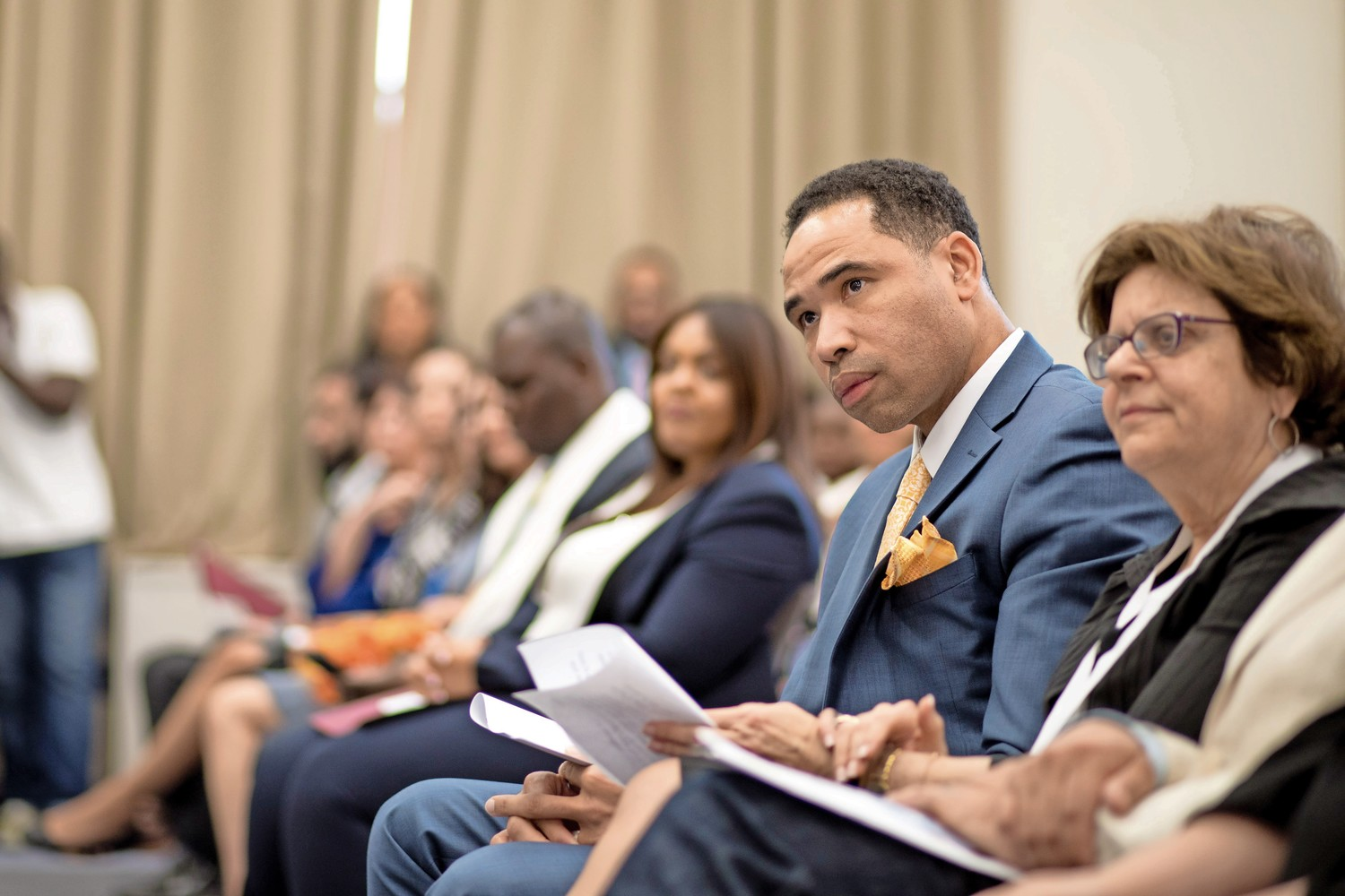 Lawrence Fauntleroy, a graduating student at Lehman College, listens as he is introduced at the school's first induction ceremony for adult degree program students into the national honor society, Upsilon Sigma of Alpha Sigma Lambda.