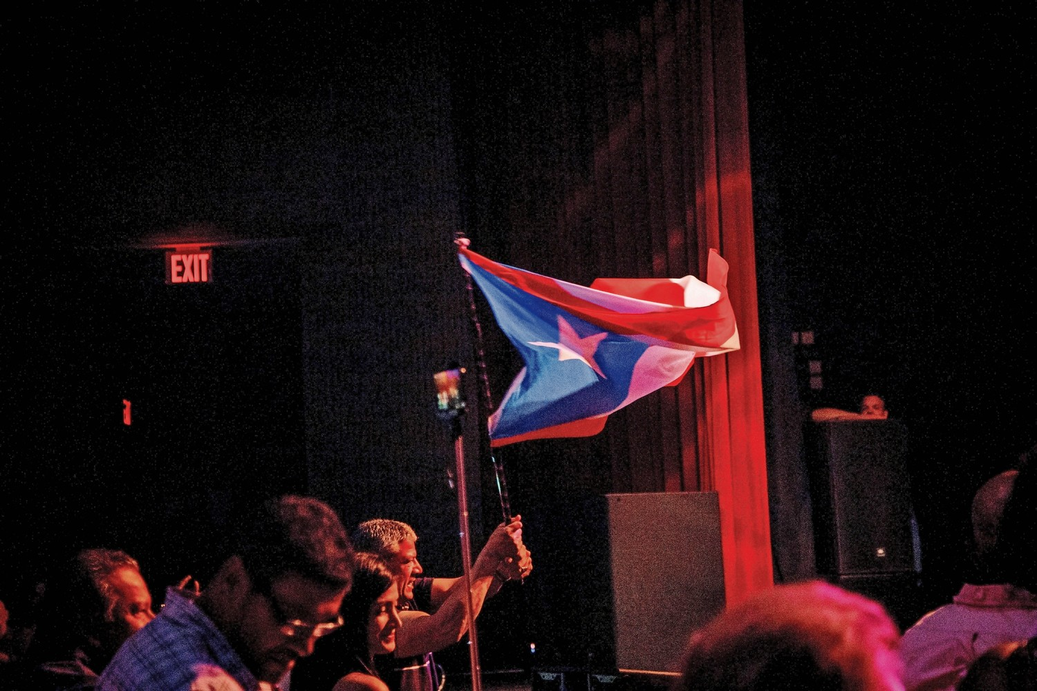 An audience member waves a Puerto Rican flag during La Sonora Ponceña's concert at the Lehman Center for the Performing Arts.