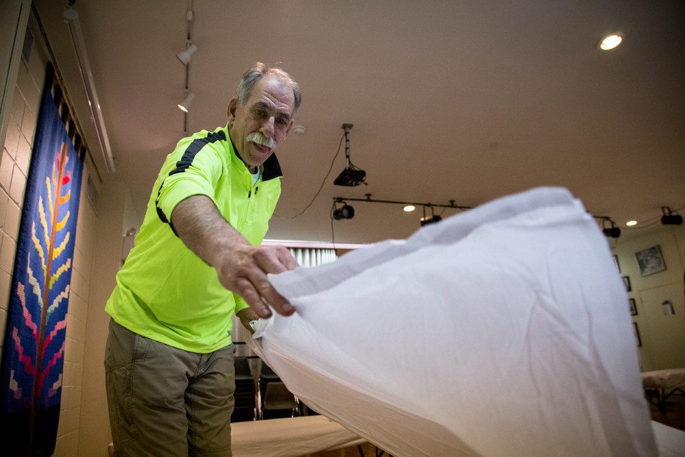 Norris Ogard, a Riverdale-based nurse practitioner, puts sheets on a cot in the Riverdale-Yonkers Society for Ethical Culture's overnight men's shelter. Ogard has been a volunteer since the shelter opened in 2003. Hebrew Institute of Riverdale wants to add options for the homeless, with plans to open its synagogue for a night each week.