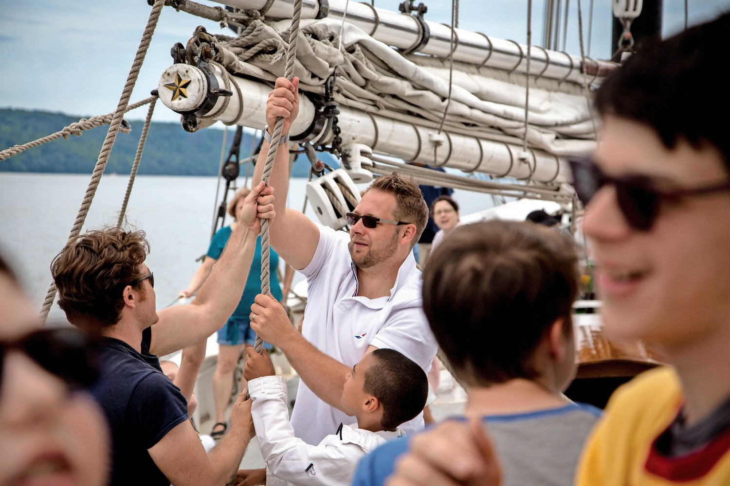 Crew members on the Pioneer schooner show would-be sailors how to raise the sails during RiverFestBX.