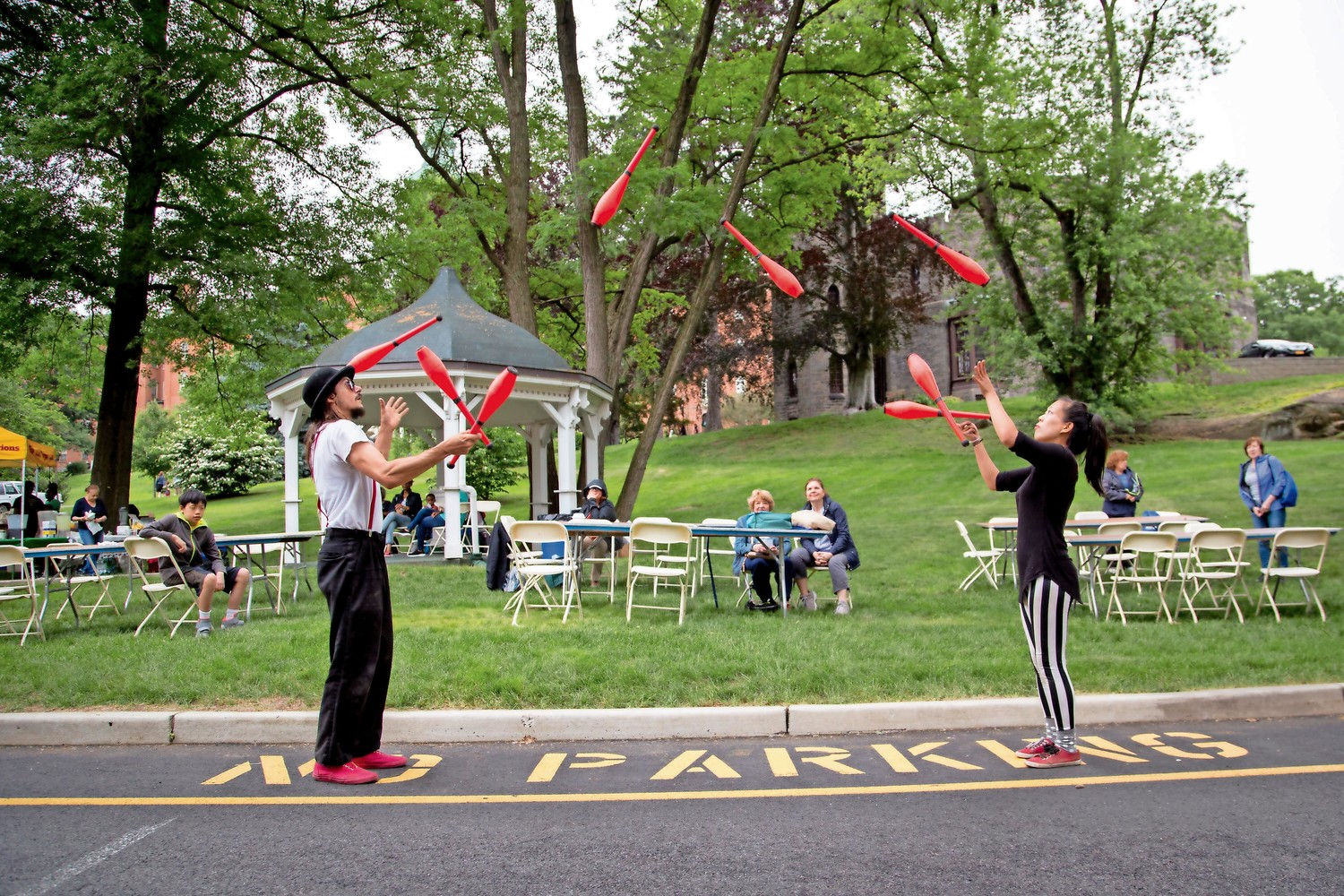 Jugglers throw pins back and forth to one another without dropping any at RiverFestBX.