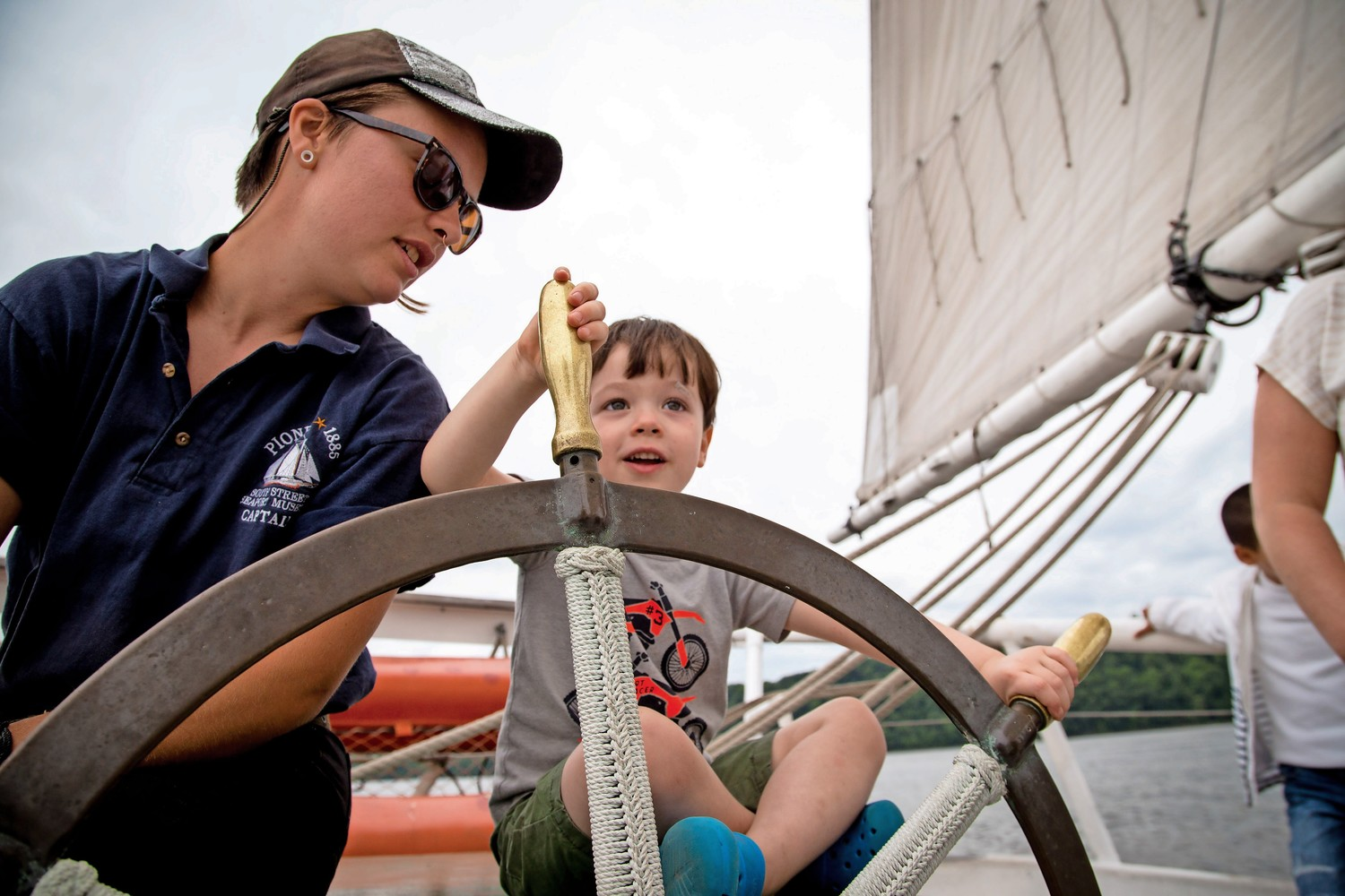 Captain Fern Hoffmann shares the steering wheel with Aaron Fitzsimmons aboard the Pioneer schooner during RiverFestBX.