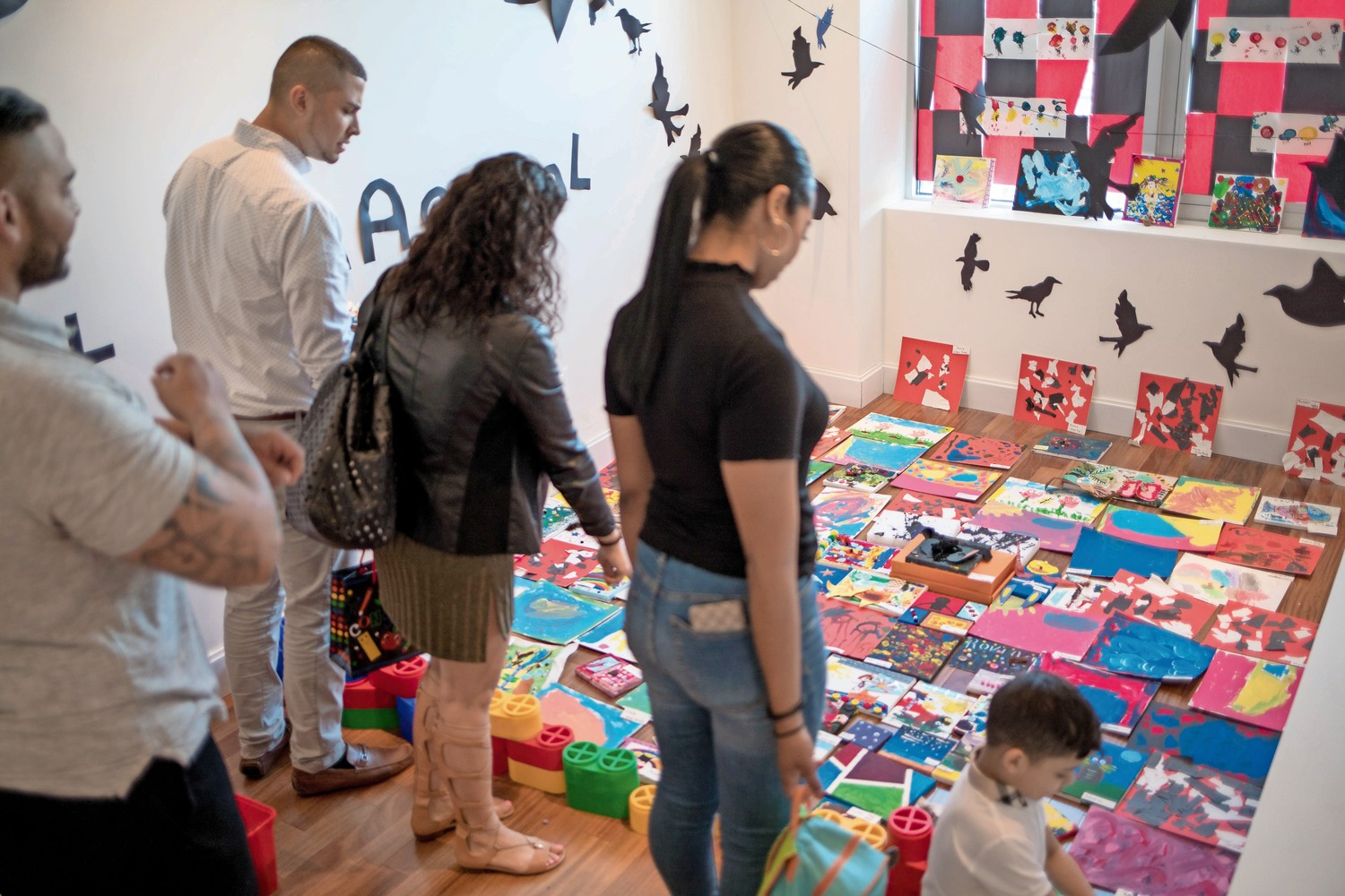 Families of students at Bedrock Preschool look at art in one of the rooms for the school's annual art gala.