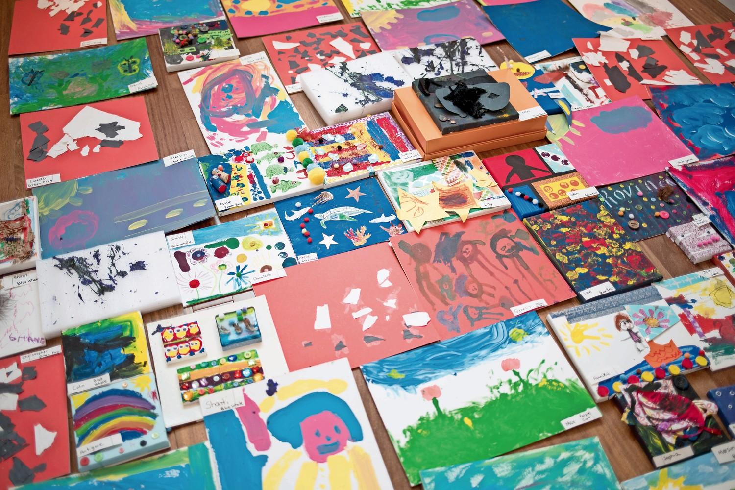 Canvases laid out on the floor show works of art that parents and children worked on together. The canvases are on display as part of the annual art gala at Bedrock Preschool.