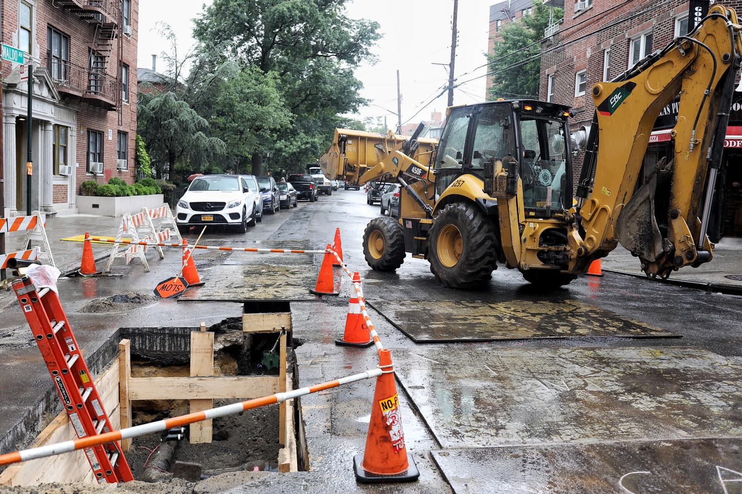 A front and backhoe loader turns onto West 238th Street from Waldo Avenue near a renovation site for a gas line. After petitioning be Assemblyman Jeffrey Dinowitz, alternate side parking rules will be suspended until August at several locations where Con Edison is doing repair work.