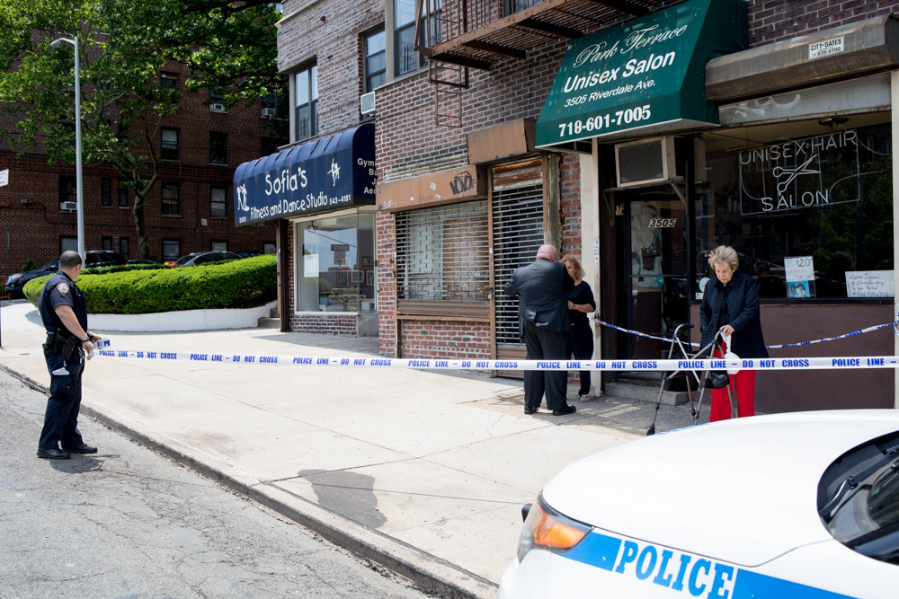 A police officer sets up a perimeter around the Park Terrace Unisex Salon on Riverdale Avenue during a robbery investigation June 7. Police later arrested Jorge Ventura in connection with that robbery and five others that hit Riverdale and Kingsbridge over the last several weeks.