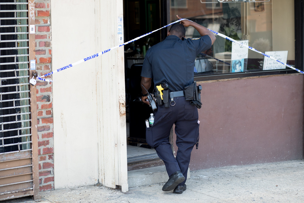 A police officer walks into Park Terrace Unisex Salon on Riverdale Avenue, one of three businesses targeted by a robber June 7. That night, police arrested Jorge Ventura, charging him with robbery and displaying a firearm in six different robberies since mid-May.