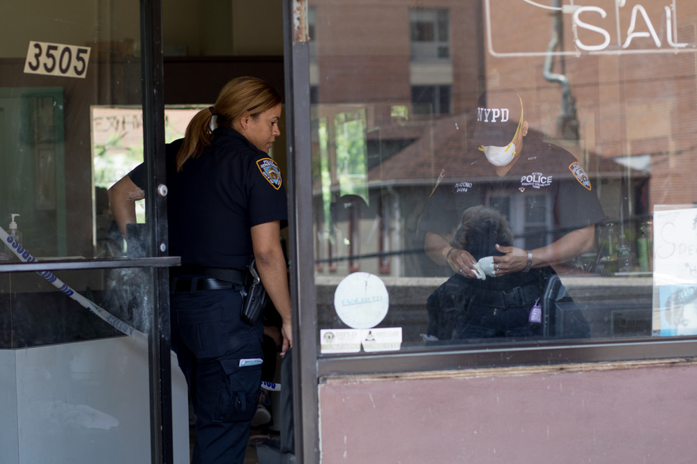 Police officers investigate a robbery at the Park Terrace Unisex Salon on Riverdale Avenue, which was targeted June 7,along with nearby DJ Drugs & Surgical and Dunkin' Donuts on West 231st Street.