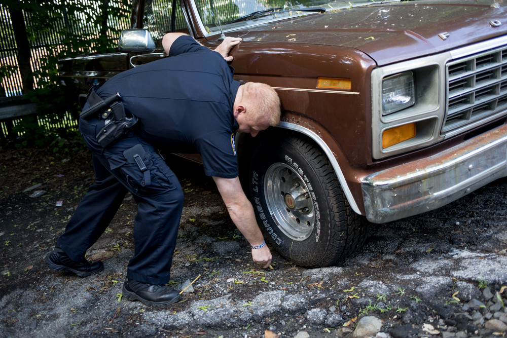 Officer Robert Edsall marks the tire of what he believes to be an abandoned car. Police must observe an abandoned car sitting on the street for at least seven consecutive days before they can have it towed away, said Sgt. Mark Giordano, neighborhood coordination officer supervisor for the 50th Precinct.