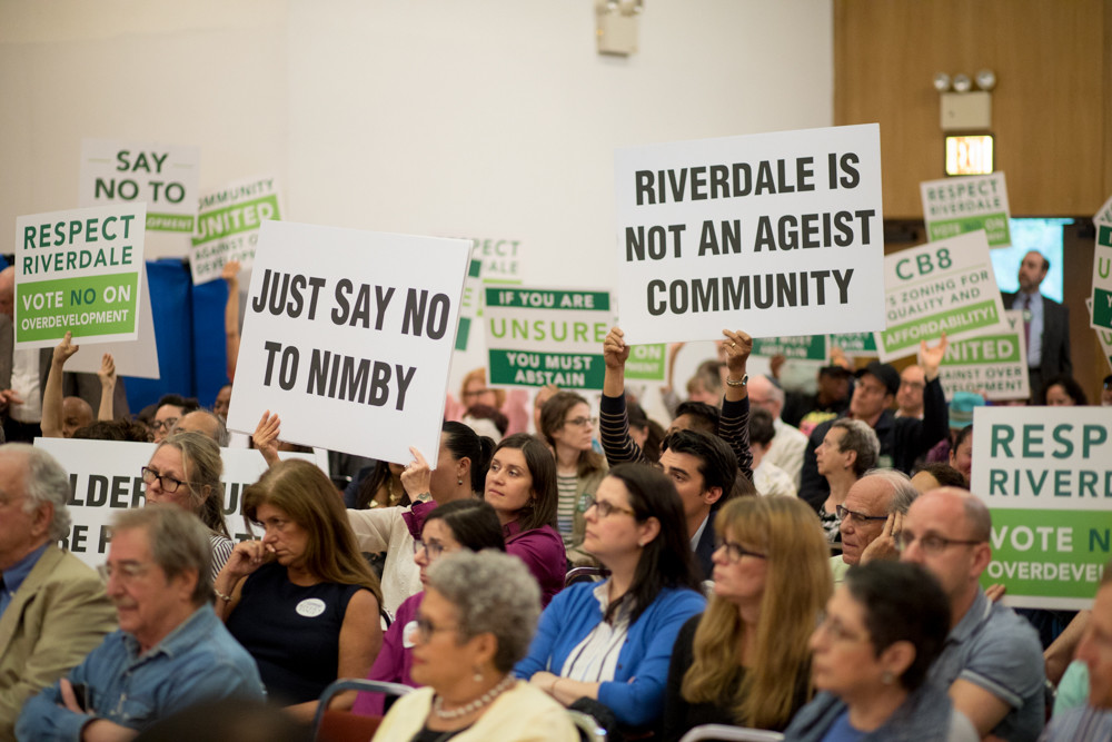 Residents on both sides of the polemical debate surrounding the Hebrew Home at Riverdale's plan to build a continuing care retirement community on its North Riverdale campus hold signs during a public hearing June 7 at Riverdale Temple.