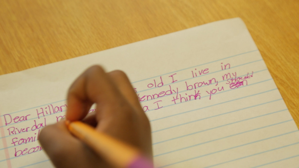 Kennedy Dupri Brown, a student at P.S. 81, writes a letter to Hillary Clinton in the short documentary film '1st Little Ladies,' which explores Clinton's influence on young girls after the 2016 presidential election. Director April Gatling-Joffee cast her daughter and several other female students from P.S. 81 to star in the film, giving them a soapbox to talk about Clinton.