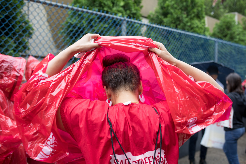 A protester puts on a poncho at a rally outside Allen Hospital just off Broadway on June 13. The New York State Nurses Association organized the rally over New York-Presbyterian's plan to decertify 30 beds in the psychiatric ward.