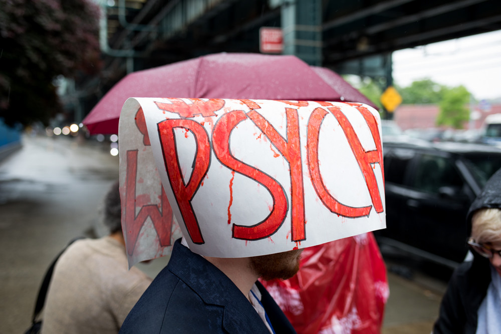 A man wears a sign on his head to guard against the rain during a rally against New York-Presbyterian's plan to decertify 30 beds in the psychiatric ward of the Allen Hospital off Broadway, just south of Marble Hill.