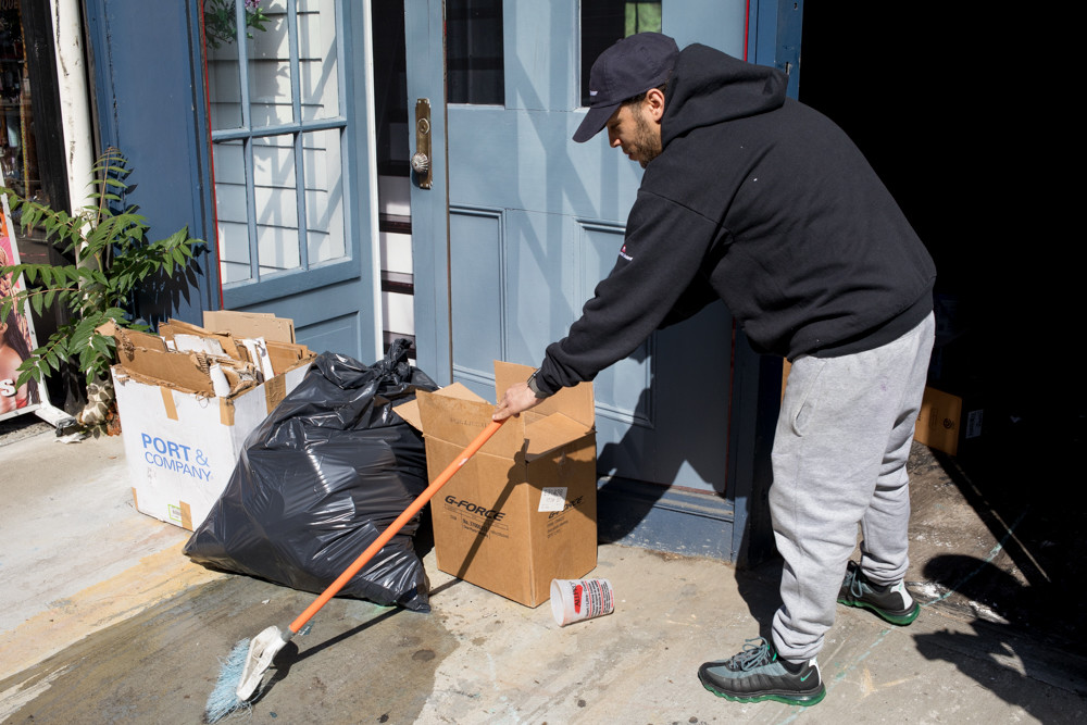 Kenny Diaz, a store manager at Tremont Paint Supply on Broadway in Kingsbridge, uses a broom and water to wash away water-based paint that leaked from a trash bag. Owner Mark Lipton pays Environmental Action Services nearly $65 a week to collect their trash.