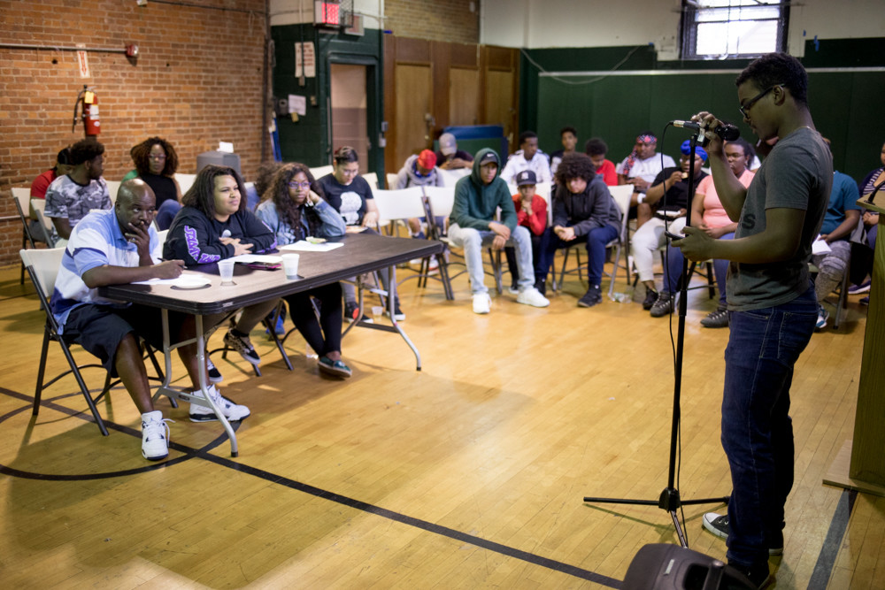 The judges and audience listen to Ancel Santana's 'Teens These Days' during a poetry slam at the Kingsbridge Heights Community Center.