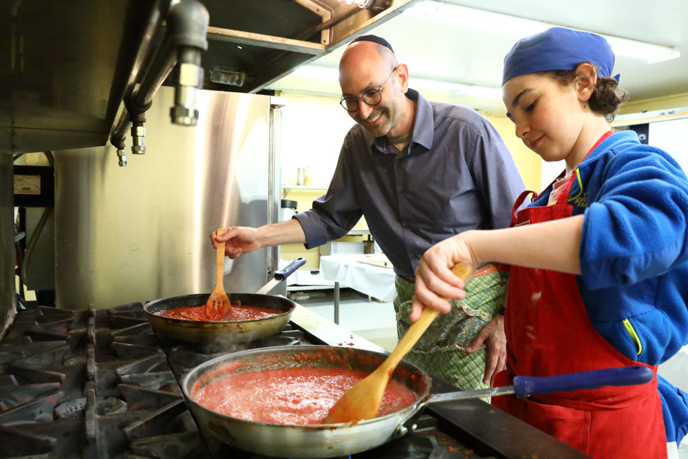 Sammy Voit and his father cook pasta sauce ahead of Sammy's bar mitzvah. An avid cook, Sammy decided to cater his entire bar mitzvah himself.