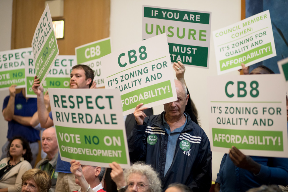 Opponents of the Hebrew Home at Riverdale's plan to build a continuing care retirement community hold signs during a Community Board 8 land use committee meeting June 7. CB8 eventually refused to give the non-profit assisted living facility its blessing in an 18-9 vote.