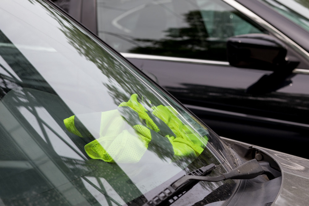 A reflective vest rests on the dashboard of a car parked in the lot at the Spuyten Duyvil Metro-North train station. Some commuters have complained of construction workers taking up parking spots that would otherwise go to Metro-North customers. But the streets are city-owned and free for anyone to park on, according to MTA officials.