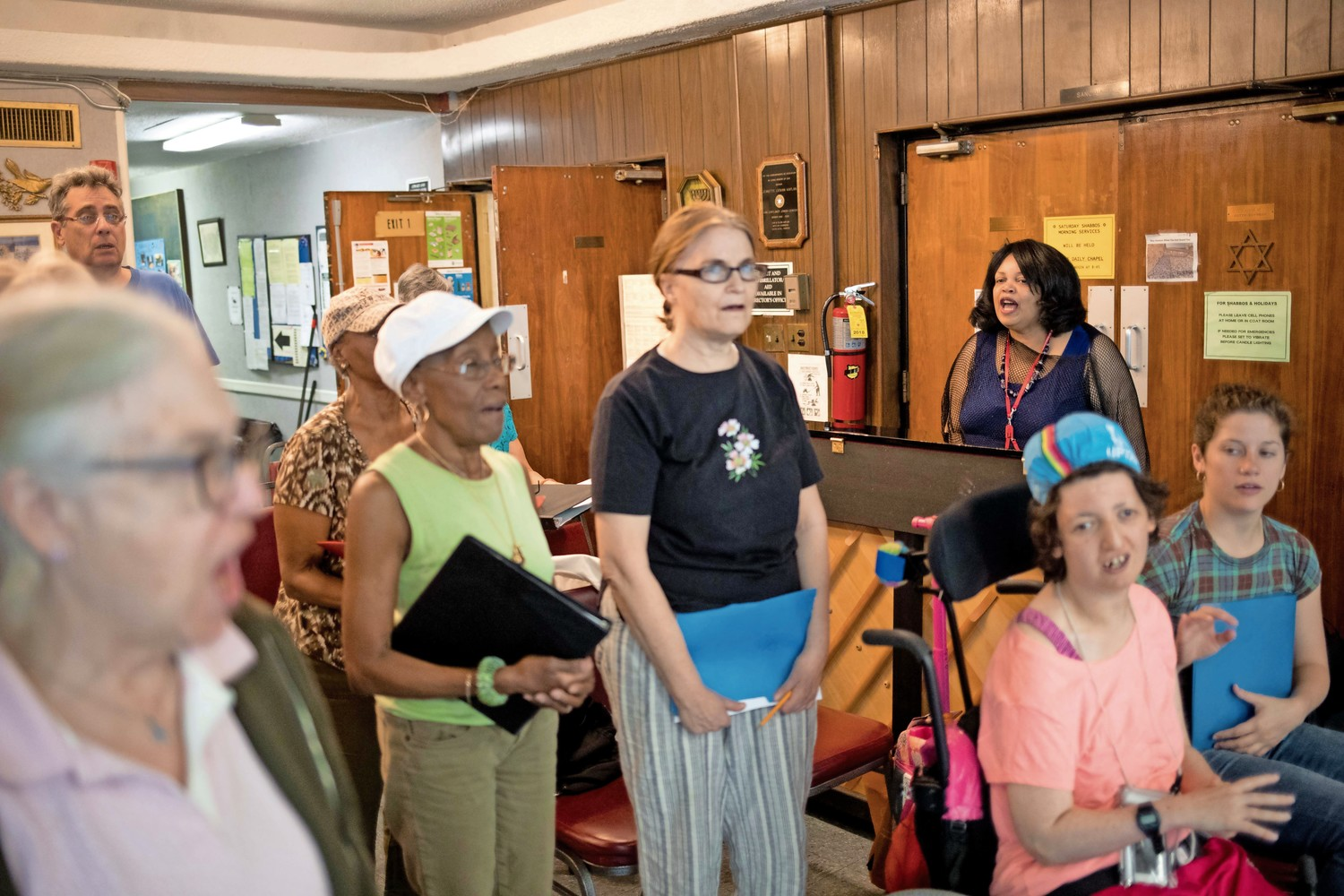 Cheryl Warfield leads singers through vocal exercises during a rehearsal at the JASA Van Cortlandt Senior Center. Warfield has been teaching senior citizens at the center how to sing for an upcoming performance on Independence Day.