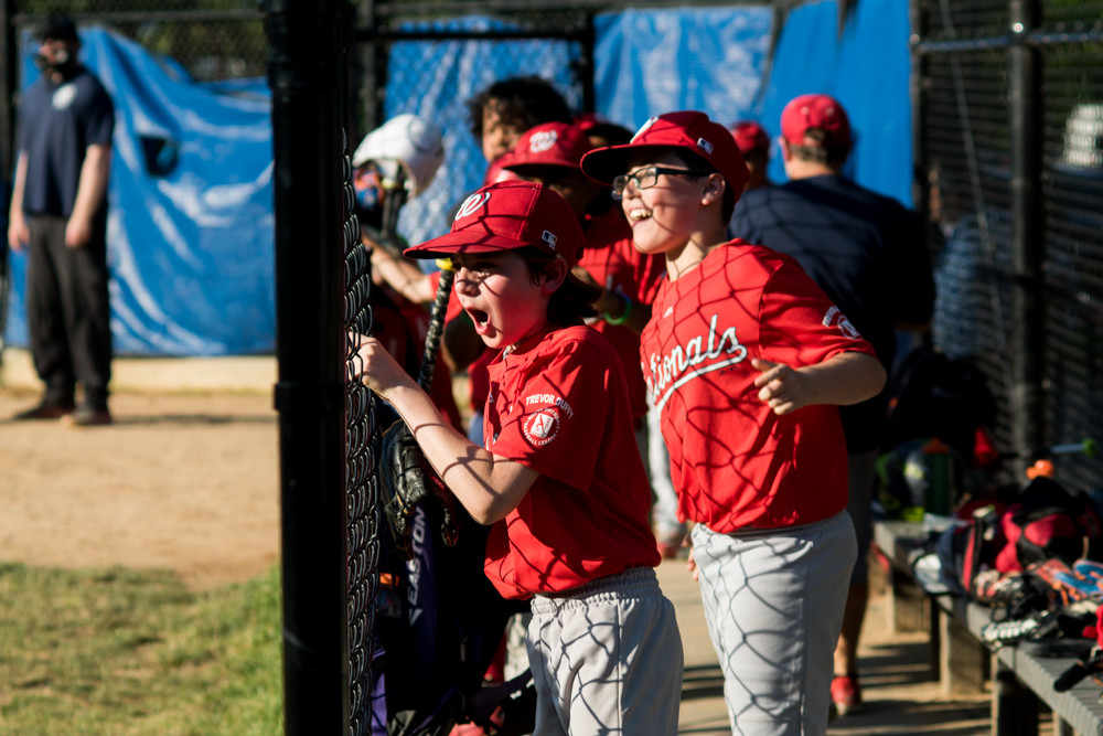 Nationals players cheer in the dugout during Game 3 of the North Riverdale Baseball League's major boys championship tournament. The Nationals beat the Yankees 7-5 to become champs.