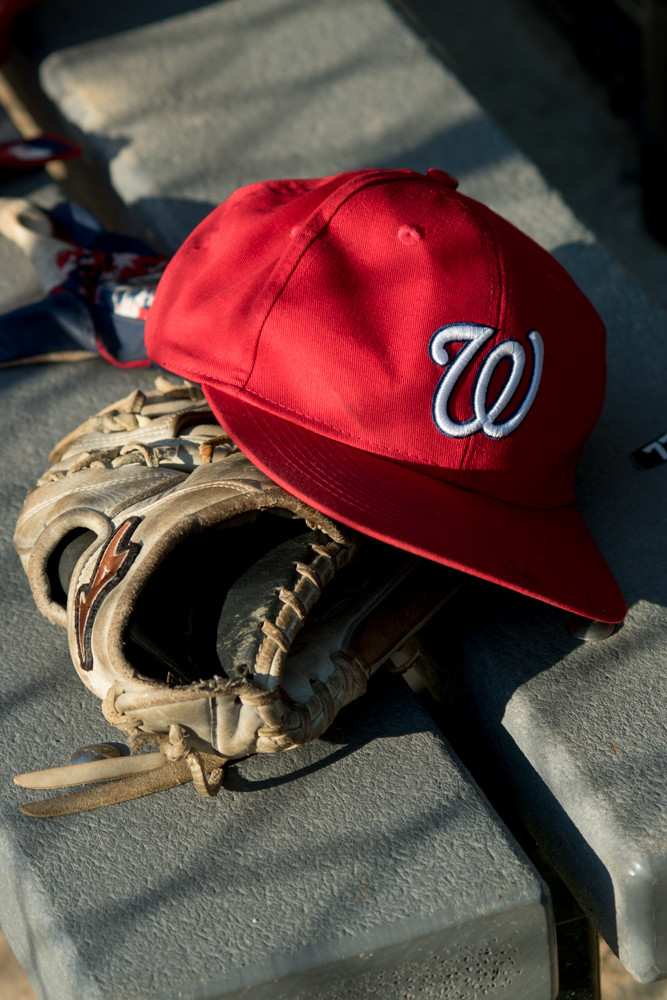 A Nationals' baseball cap rests on a mitt in the dugout during Game 3 of the North Riverdale Baseball League's major boys championship tournament.