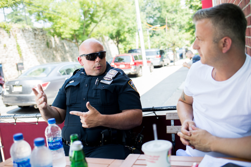 50th Precinct officer John Labianca talks about neighborhood policing with Mario Curanaj, owner of Salvatore's of Soho on West 238th Street and Riverdale Avenue. Since the 5-0 introduced the neighborhood coordination officer program last April, Labianca says he's noticed 'more positivity from the community.'