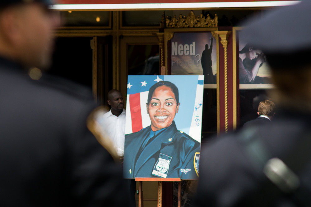 A portrait of the late NYPD officer Miosotis Familia stands outside of World Changers Church last year.
