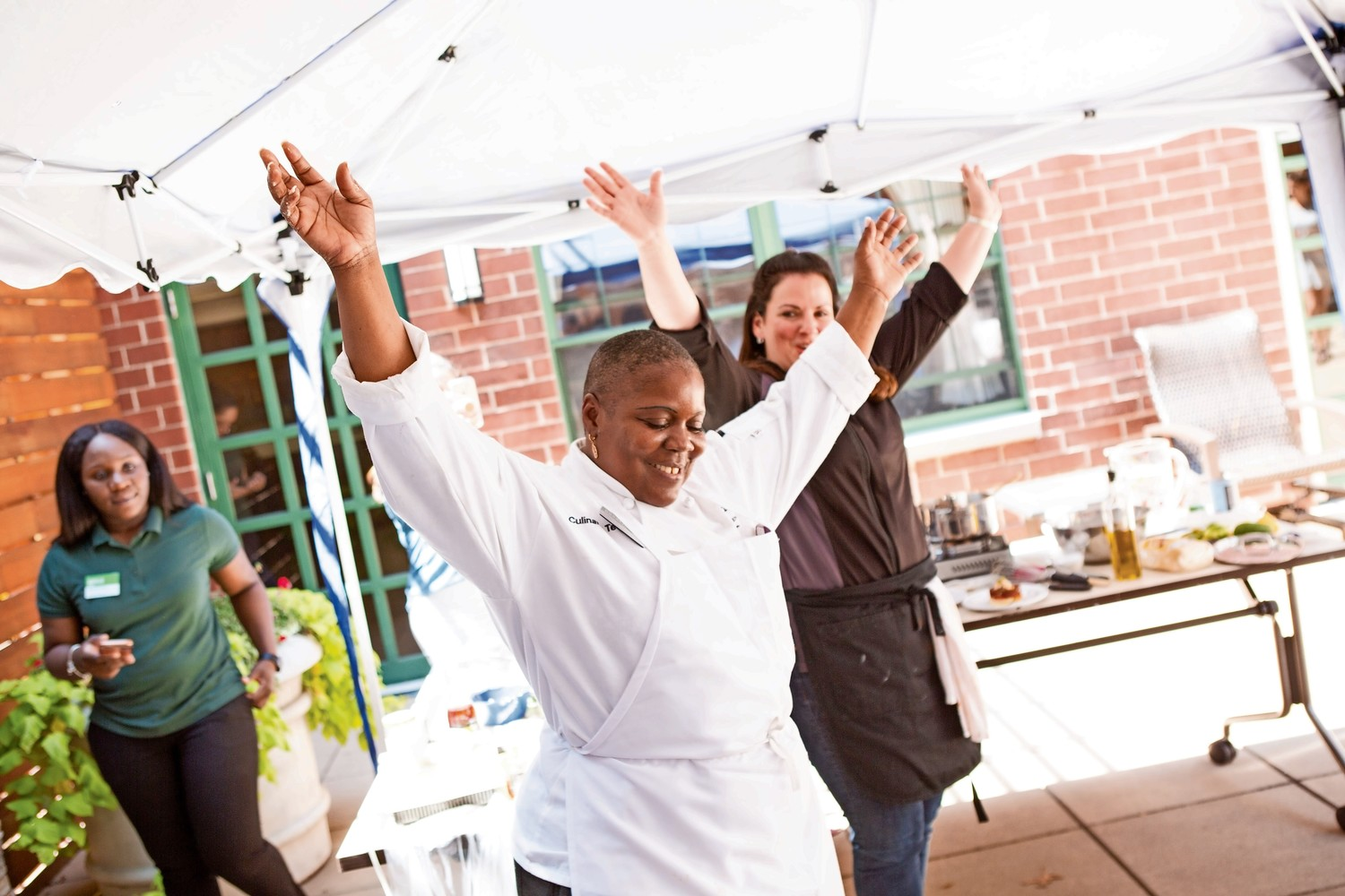 Atria chef Rosalind Craft and food blogger Rachel Berger hold up their hands to show that they have finished cooking at the conclusion of Atria's Chef Showdown. The cooking competition returns to Atria for its third installment on July 17.