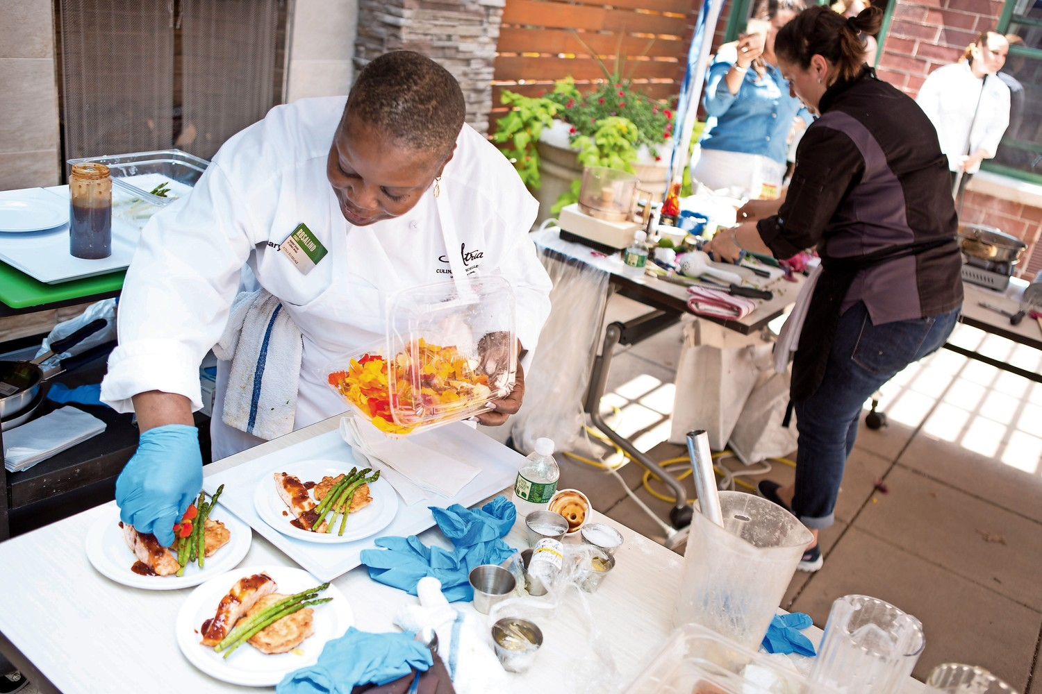Atria chef Rosalind Craft, left garnishes a plate of corn fitters, teriyaki glazed salmon and asparagus while food blogger Rachel Berger, right, slices onions for her dish at Atria Riverdale's Chef Showdown last year. The cooking competition returns to Atria for its third installment on July 17.