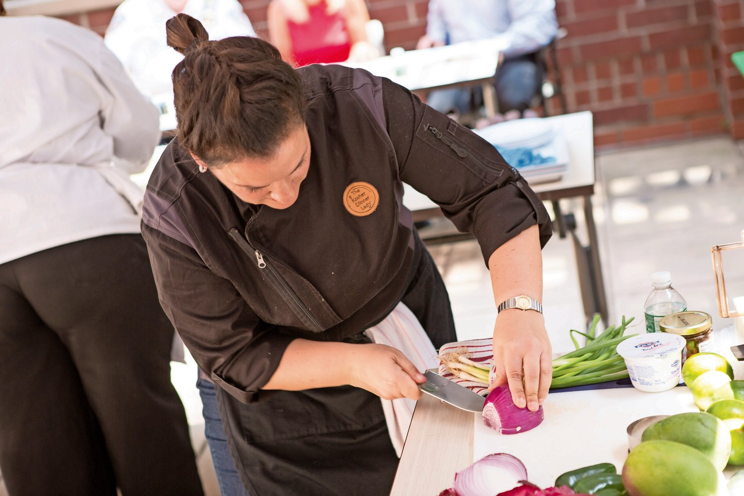 Food blogger Rachel Berger slices onions for her dish at Atria Riverdale's Chef Showdown last year. The cooking competition returns to Atria for its third installment on July 17.