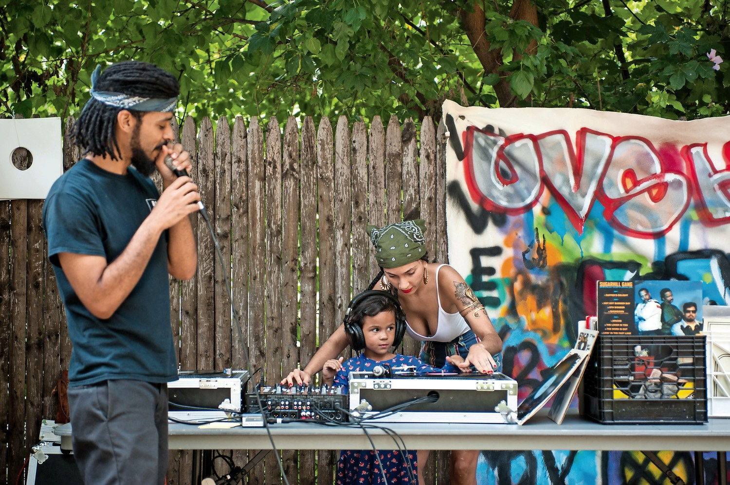 Sunny Vazquez, one of the co-founders of Uptown Vinyl Supreme and co-founder of the Hip-Hop Summer School course at the Kingsbridge Heights Community Center, helps student Scarlett Gomez scratch a record at the summer jam to celebrate the end of the five-week course.