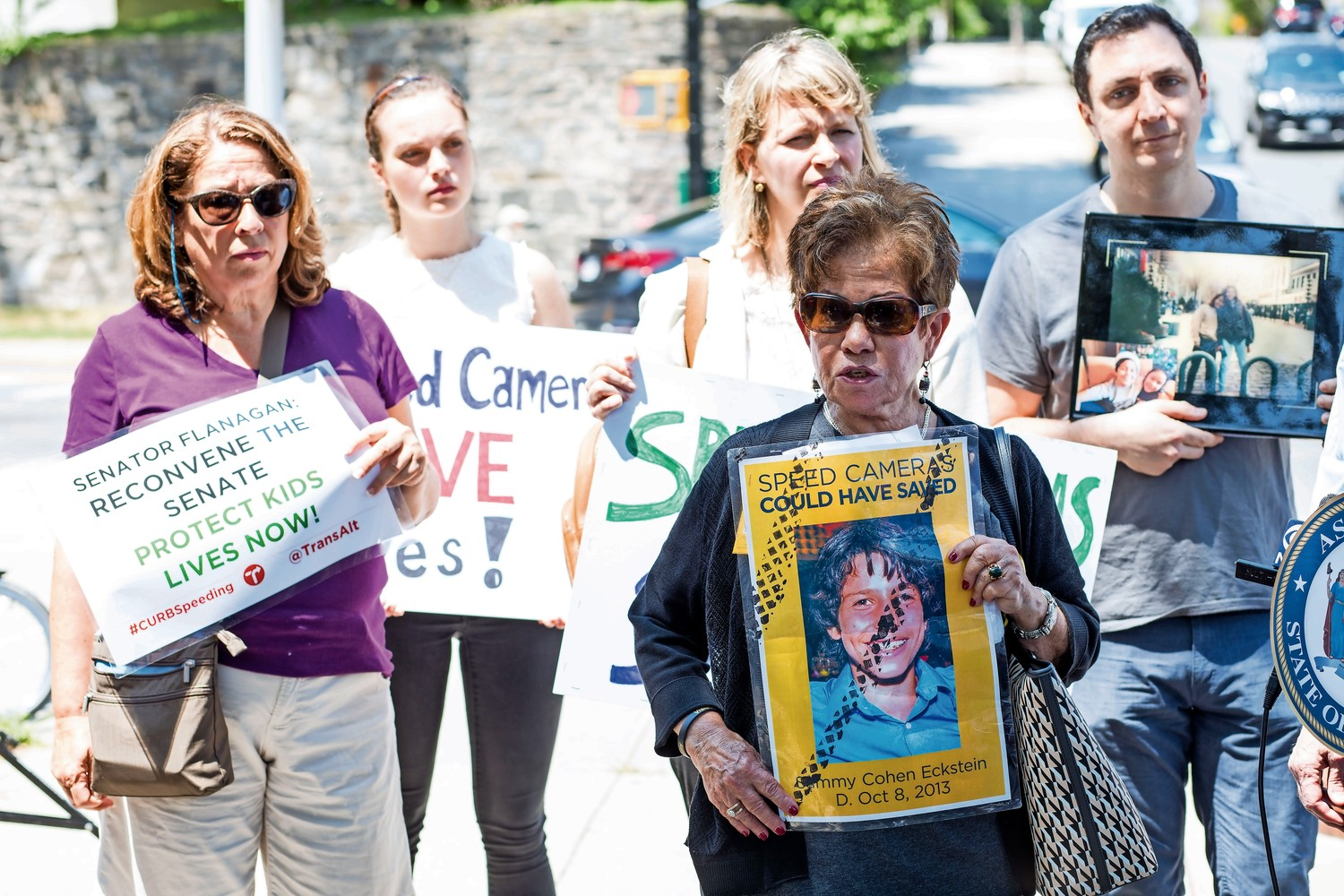 Residents hold signs in favor of speed cameras at a press conference outside of P.S. 81 on July 12. The speed camera program is set to expire on July 25, which residents and local lawmakers feel is a mistake.