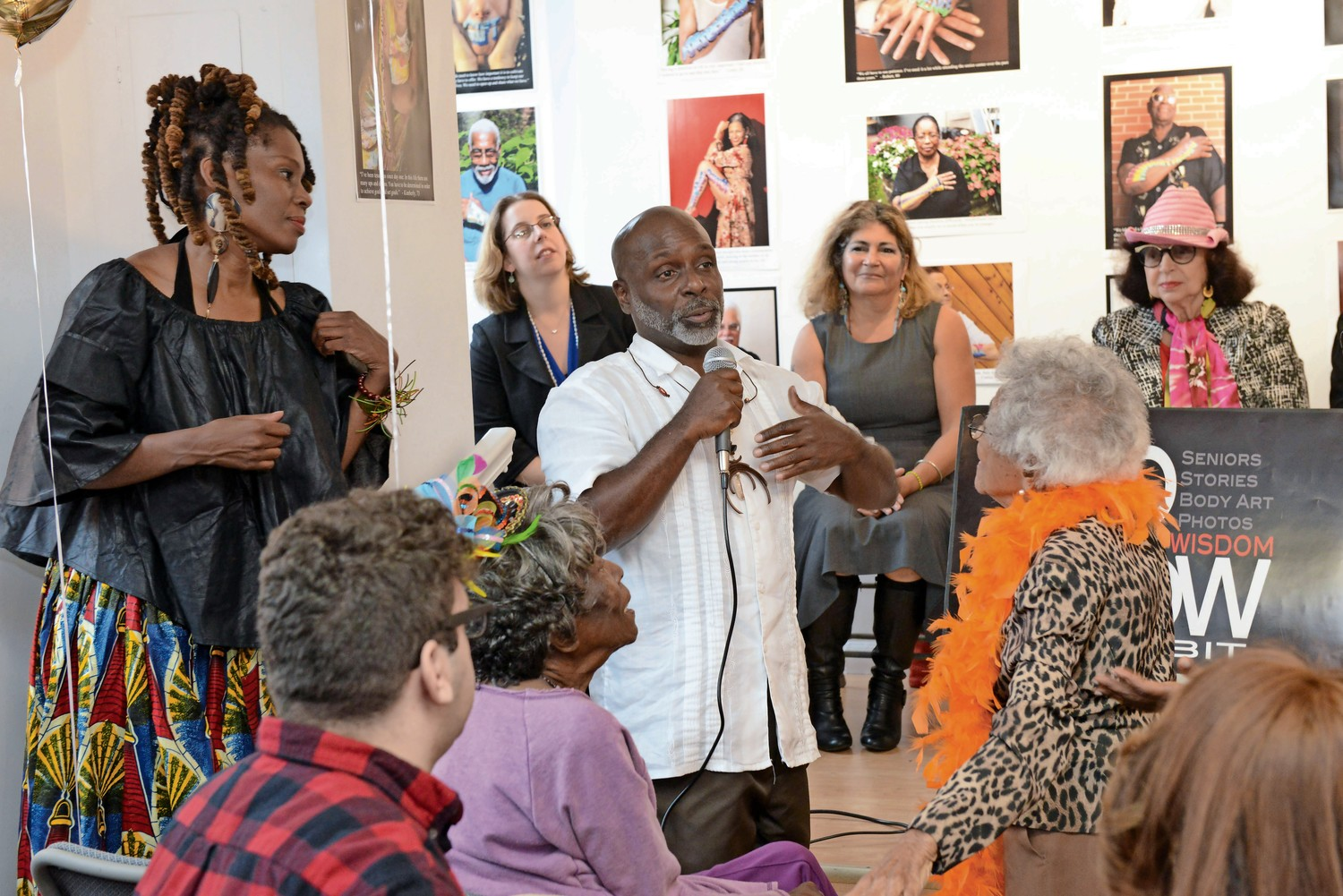 Evan Bishop speaks at the opening of his exhibition for '100 Words of Wisdom' last year. For the series, Bishop and his partner Katori Walker asked elderly people to share one word of wisdom, which Bishop and Walker then painted on each person.