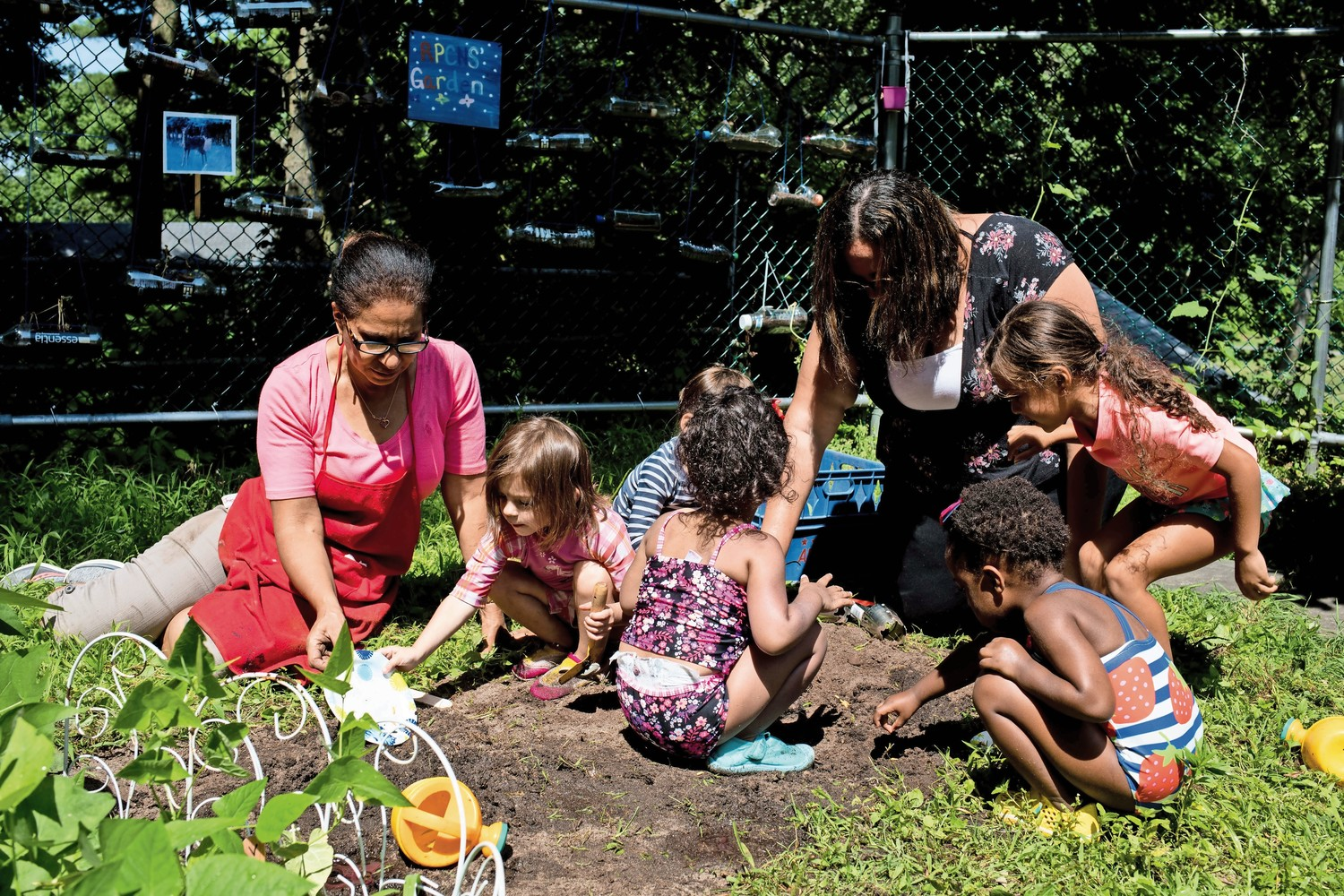 Students and teachers at Riverdale Presbyterian Church Nursery School plant fruit seeds as part of the school's 'Explorations in Nature' summer program.
