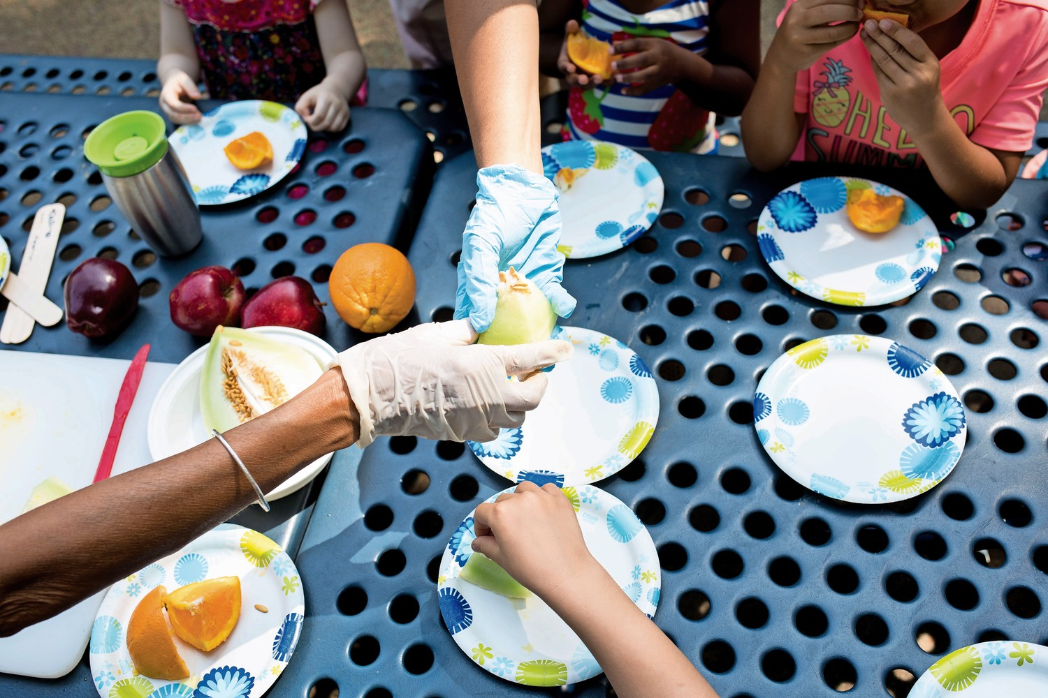Teachers at Riverdale Presbyterian Church Nursery School pass around pieces of fruit for students to eat. After snacking on the fruit, the students will collect and plant the seeds in the garden as part of the school's 'Explorations in Nature' summer program.