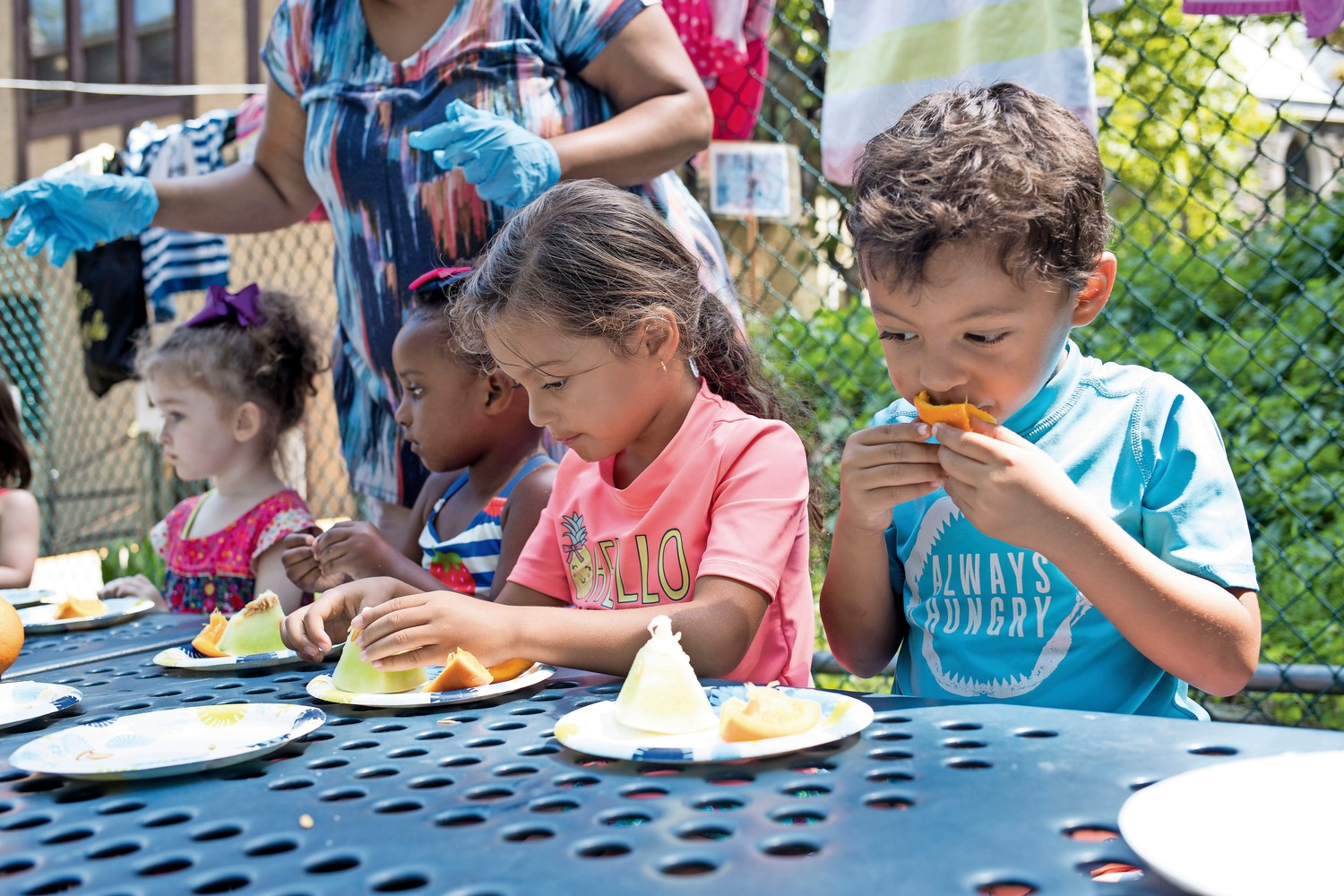 Students at Riverdale Presbyterian Church Nursery School eat fruit and collect seeds from the fruit that they will then plant in the garden as part of the school's 'Explorations in Nature' summer program.