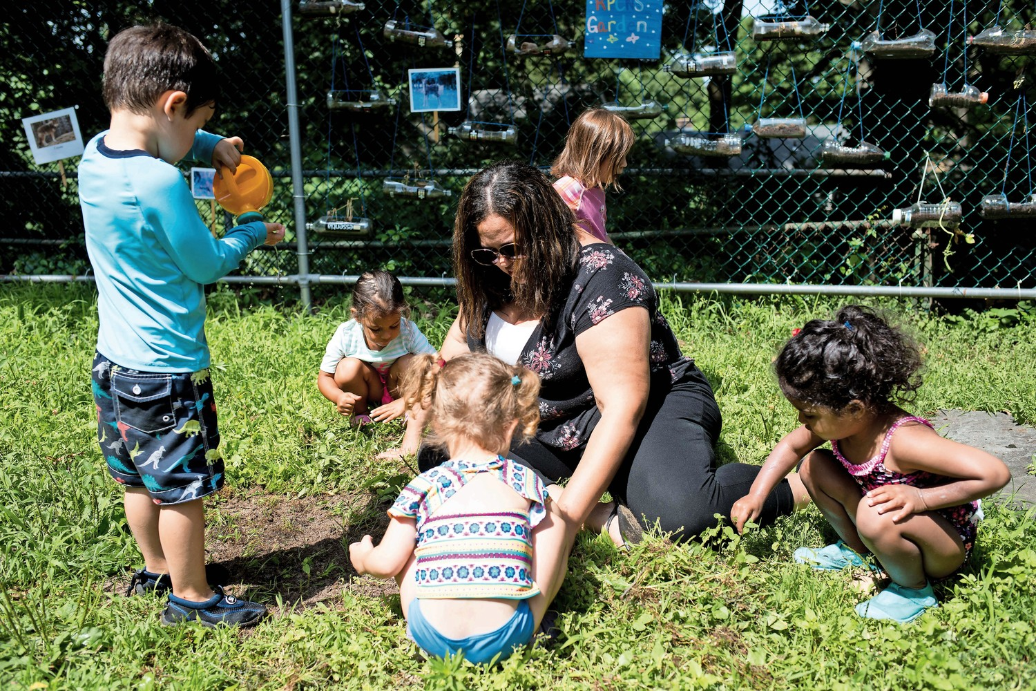 Yadhira Reyes, a teacher at Riverdale Presbyterian Church Nursery School, helps students prepare the soil for planting seeds as part of the school's 'Explorations in Nature' summer program.