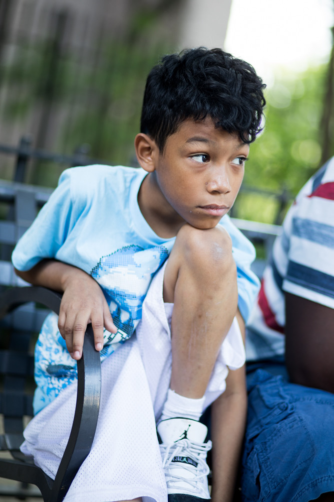 Jovan Lopez, 10, looks out as his mother, Anjanette Delgado, talks about her family's experience living in the New York City Housing Authority's Bailey Houses on Heath Avenue. Delgado wants Jovan tested for lead, which can cause developmental delays in young children, according to the Centers for Disease Control and Prevention.