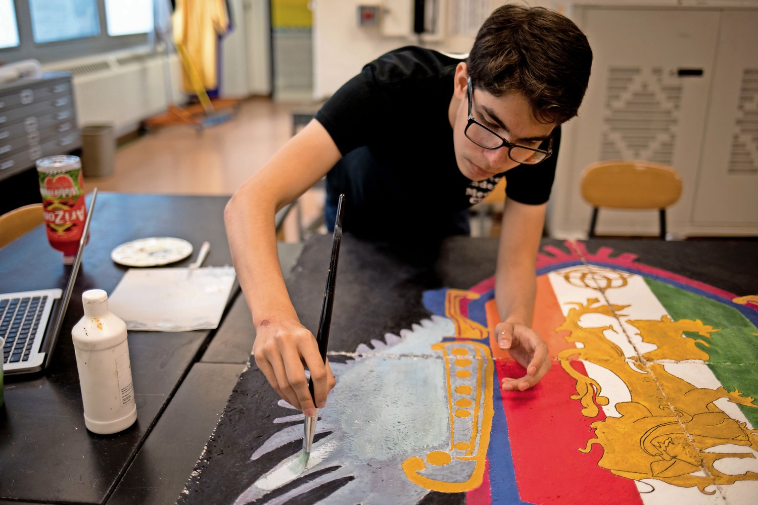 Saige Welsh paints a ceiling tile in the art classroom at IN-Tech Academy. Welsh, who will be a junior next year, is one of many students who will dearly miss Bruno Santini, a beloved art teacher at the school who recently retired.