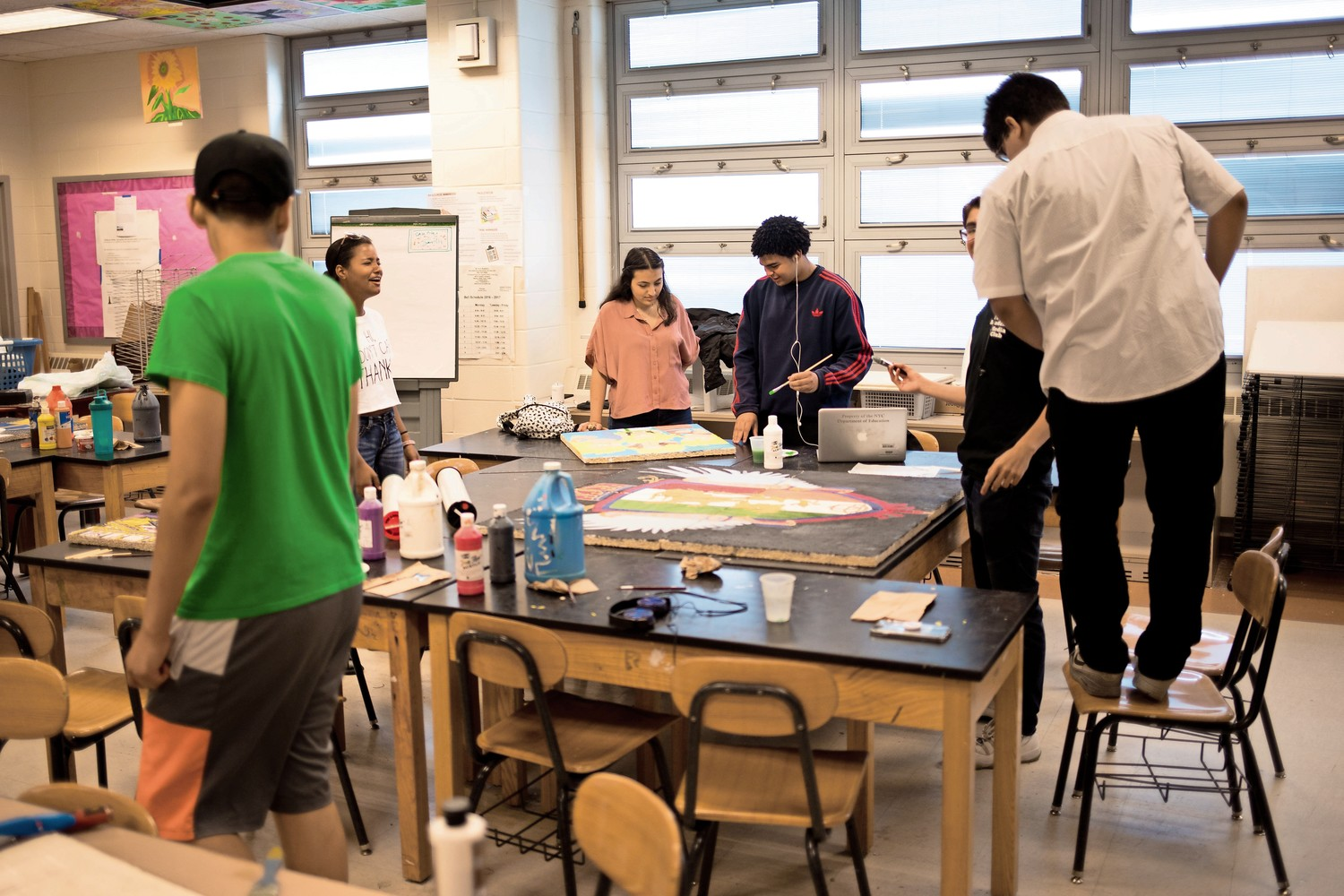 IN-Tech Academy students paint ceiling tiles in the art classroom. Painted ceiling tiles can be found throughout the school. The practice began with Bruno Santini, a newly-retired art teacher.
