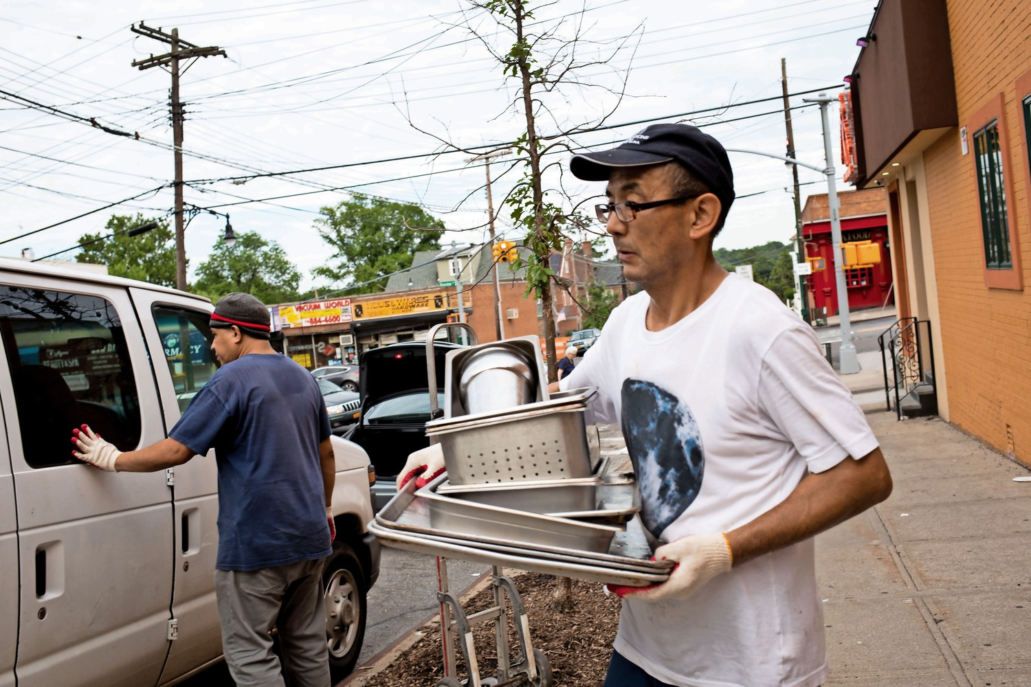 A man carries various kitchen appliances out of K Grill House on July 31. The North Riverdale eatery has closed down for unspecified reasons.