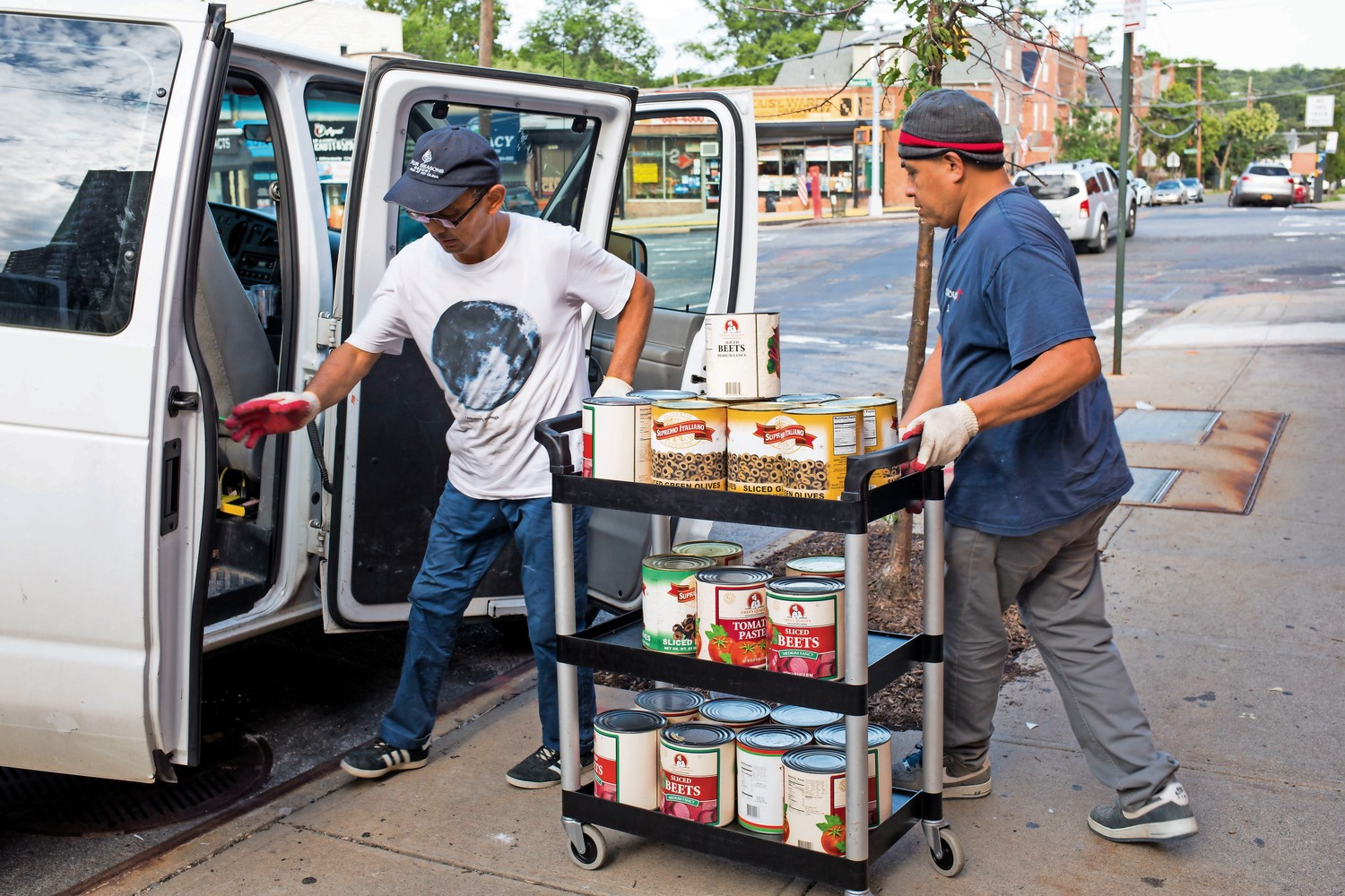 People roll a cart with various foodstuffs towards a white van parked outside K Grill House on West 259th Street. The North Riverdale eatery closed down for unspecified reasons.