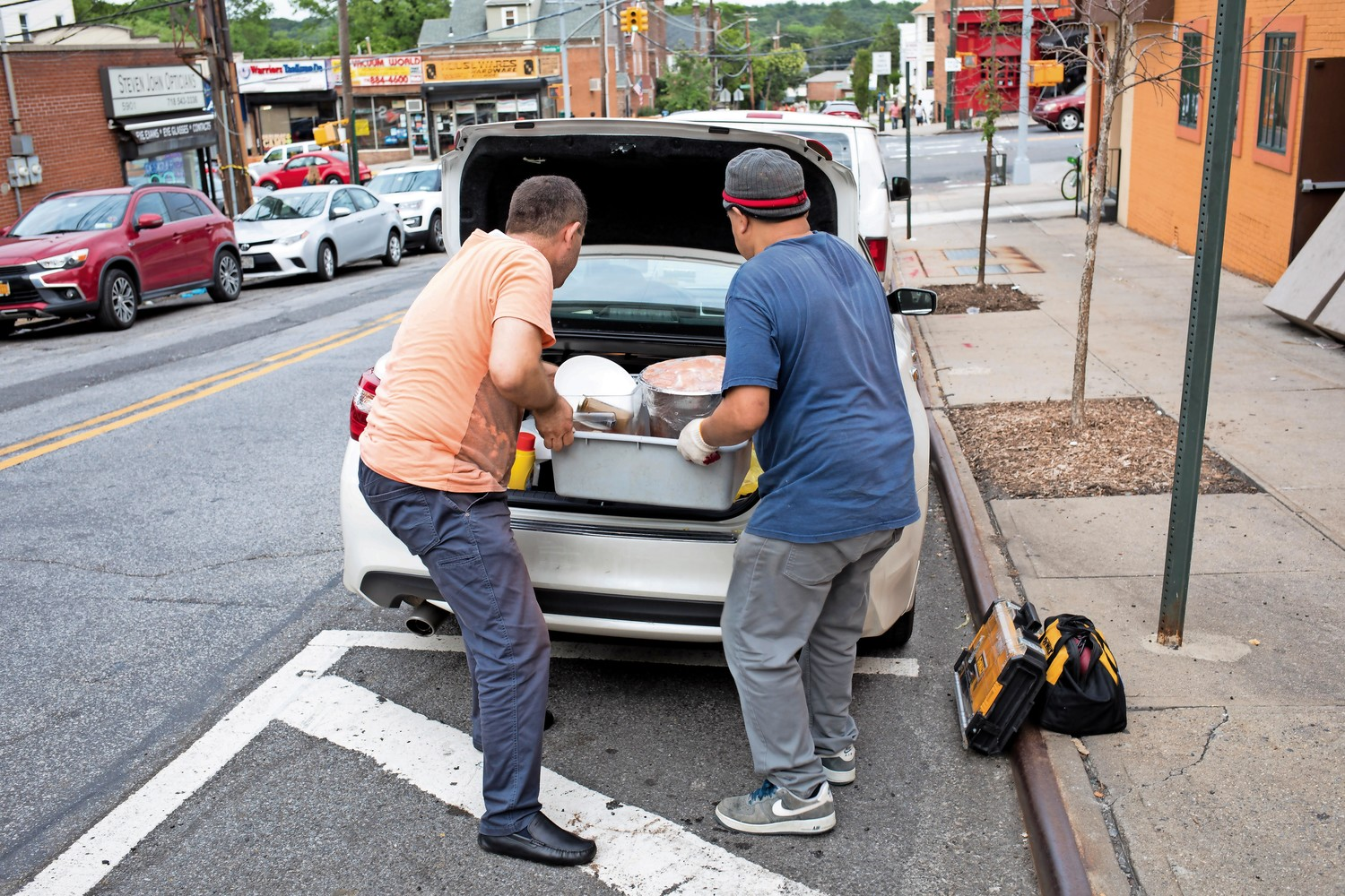 People load kitchen appliances and raw food into the back of a car outside K Grill House, which closed down for unspecified reasons.