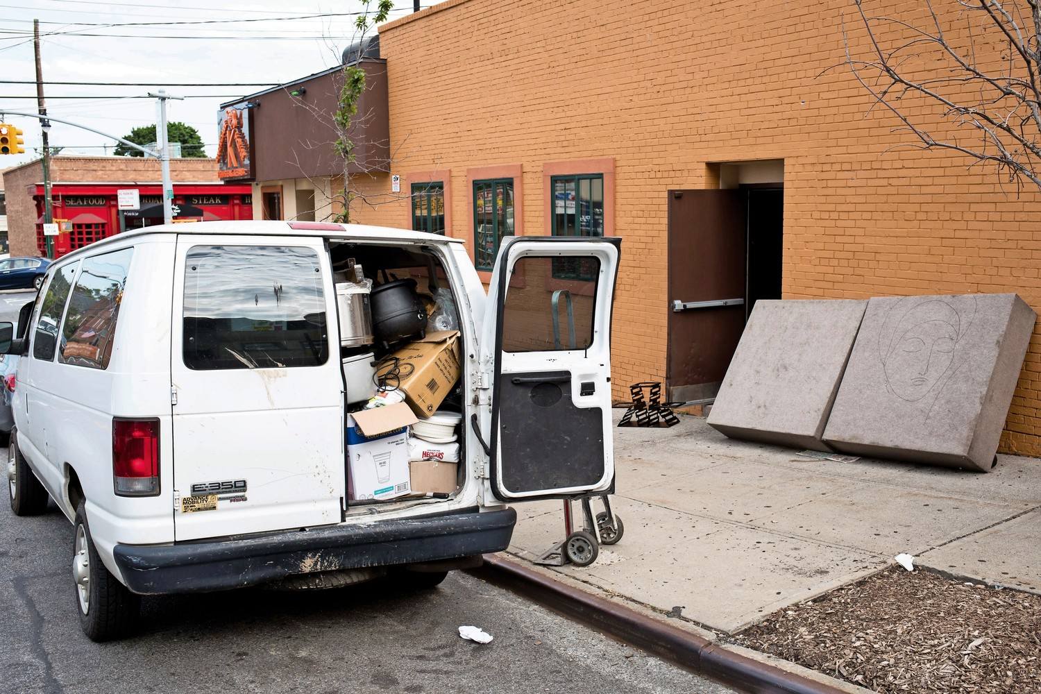A white van packed with appliances and foodstuffs sits outside of K Grill House, which closed down for unspecified reasons.