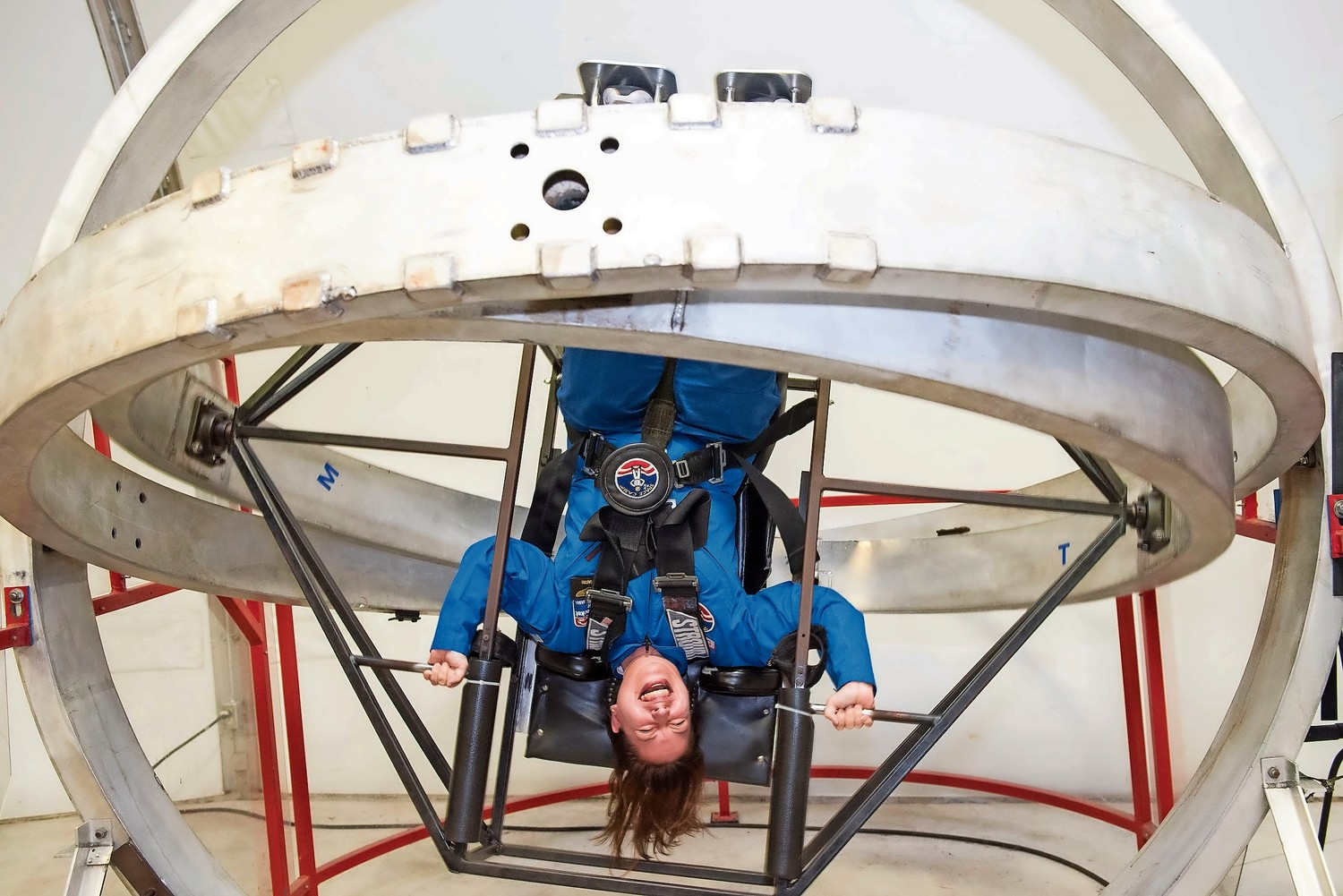 Carolina Castro, a science teacher at Riverdale/Kingsbridge Academy, hangs upside down in a multi-axis trainer during the program Honeywell Educators at Space Academy in Huntsville, Alabama. An essential part of astronaut training, the multi-axis trainer is meant to simulate what would happen if a spacecraft went into an uncontrolled spin in space.