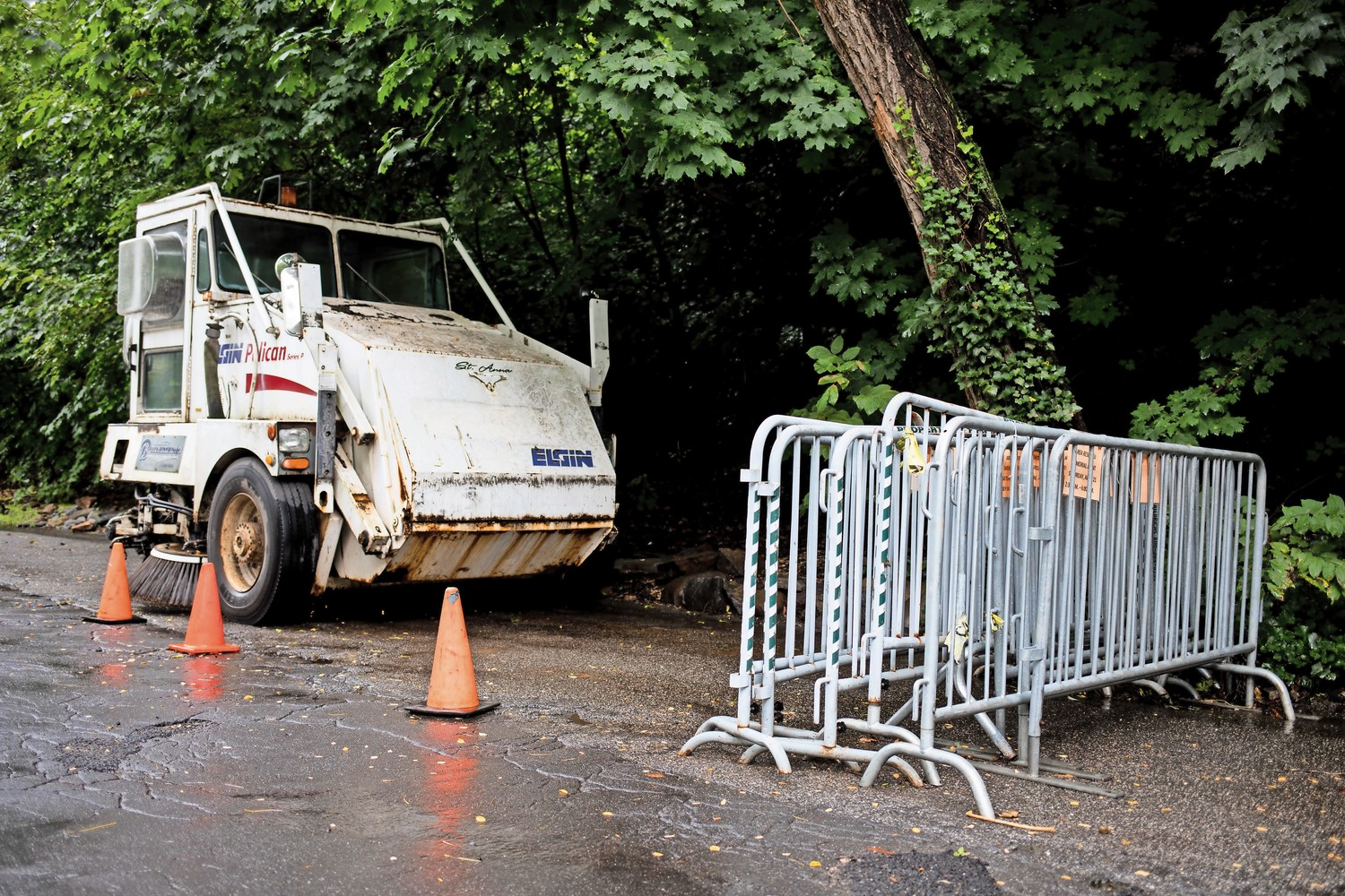 A collection of barricades and a street cleaning vehicle stand on the side of Fieldston Road. The neighborhood will close its streets to public traffic and commercial vehicles on Aug. 17 and 18.